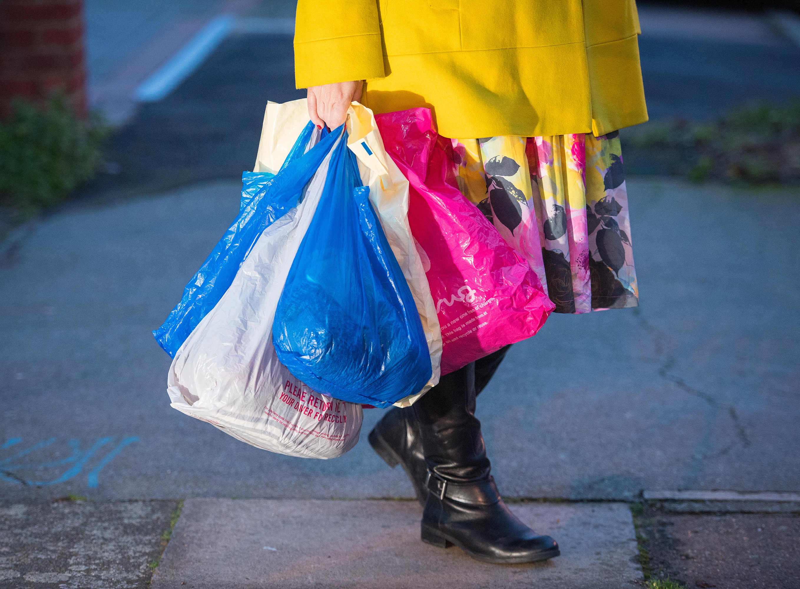 woman carrying plastic bags