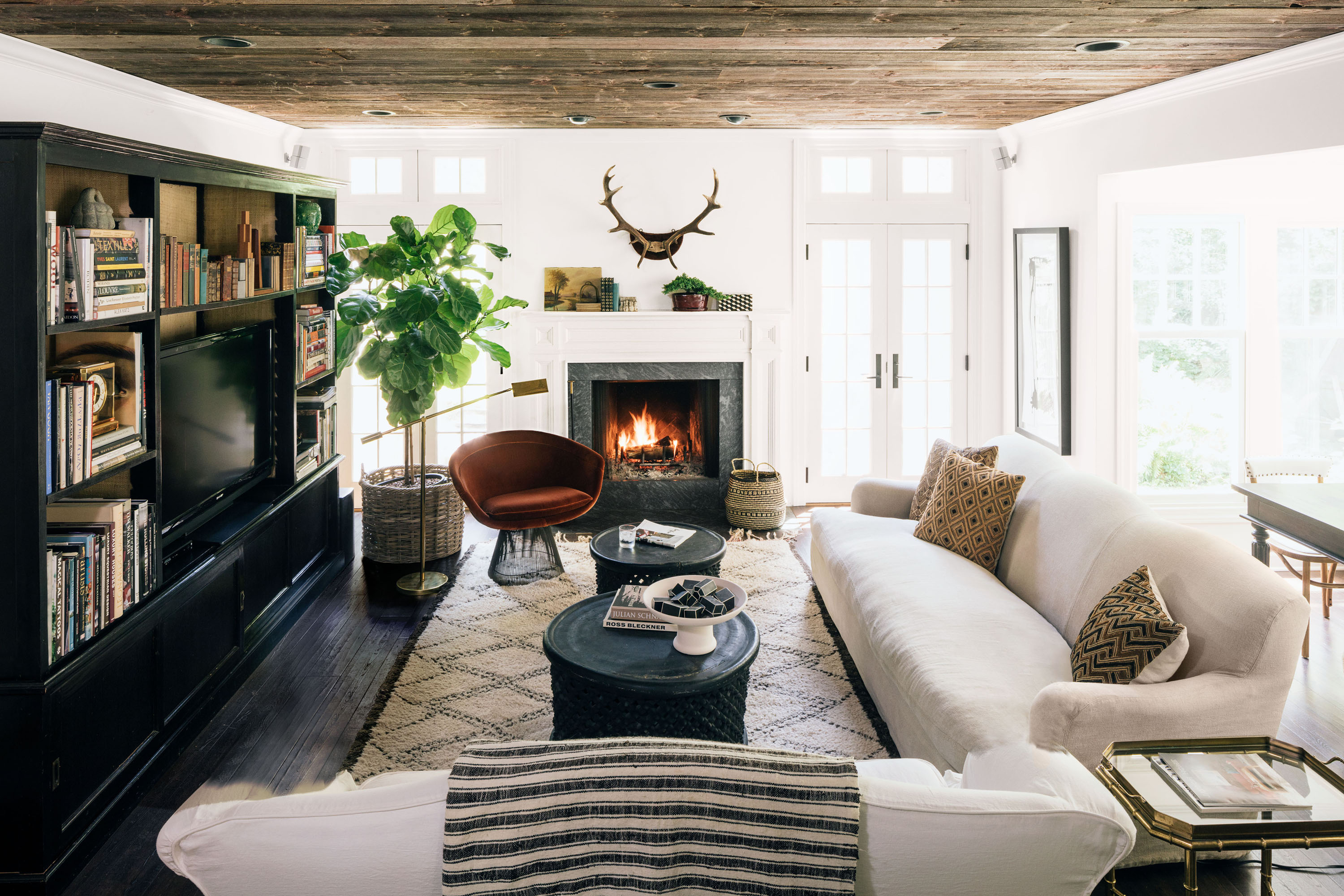 neutral family room with velvet chair and antlers hanging above fireplace