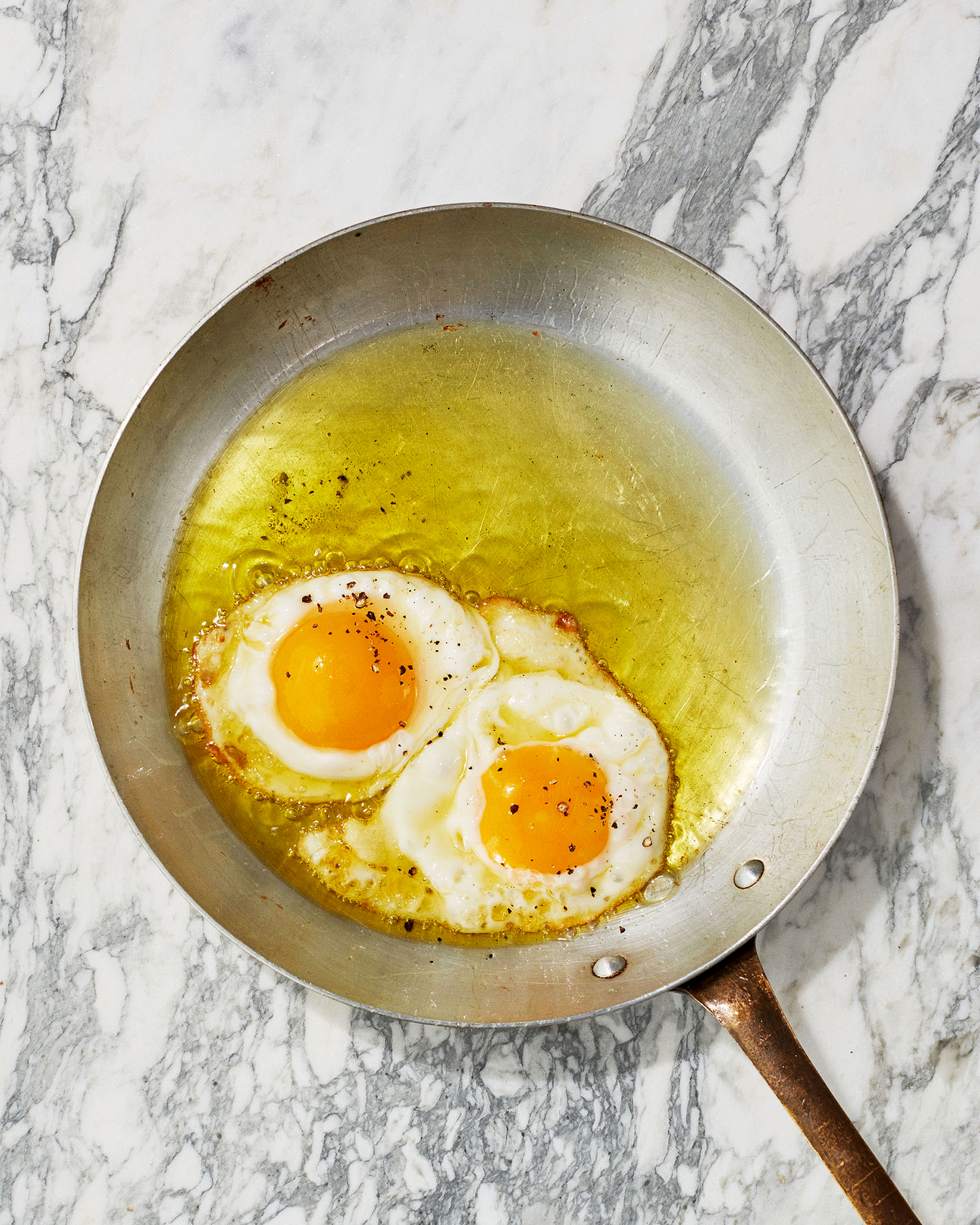 olive-oil fried eggs in pan