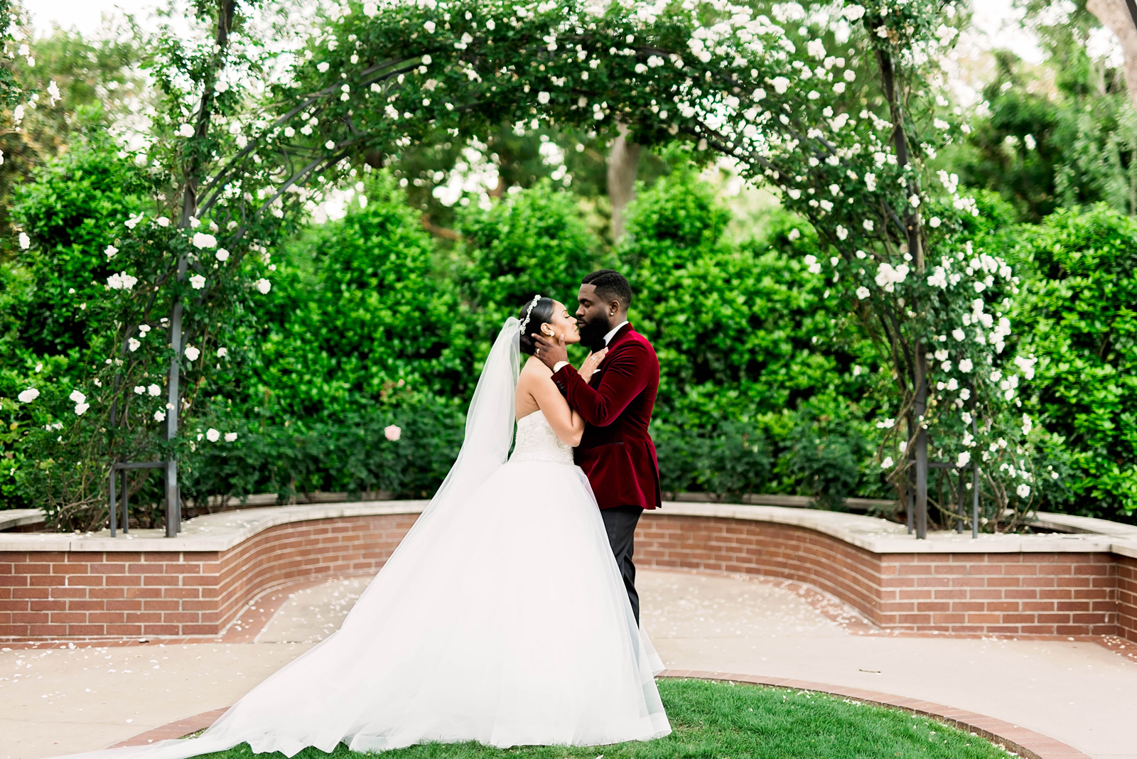 bride and groom kiss outside under greenery arch