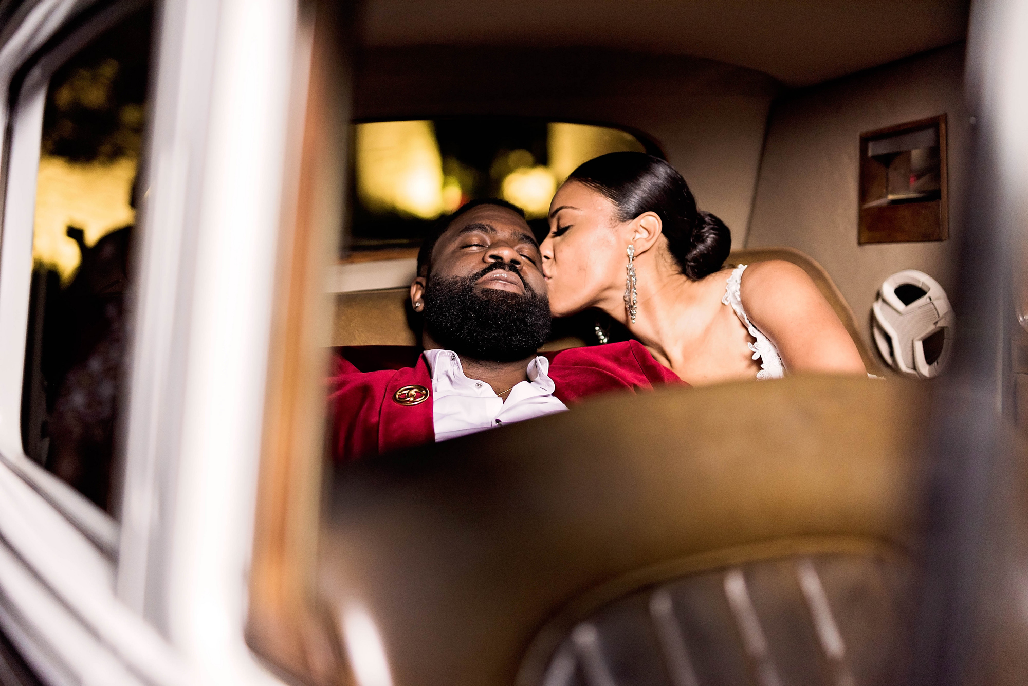 bride and groom sitting in back seat of car