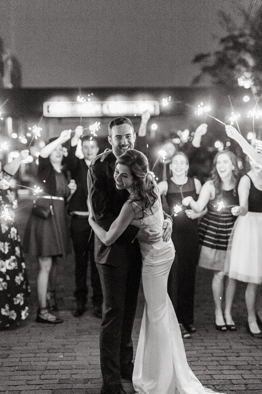 bride and groom surrounded by guests with sparklers for sendoff