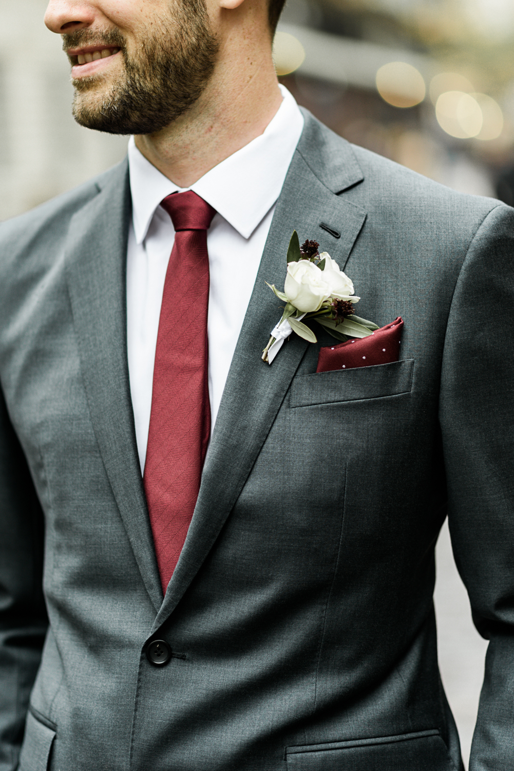groom wearing custom charcoal suit with a burgundy tie and pocket square