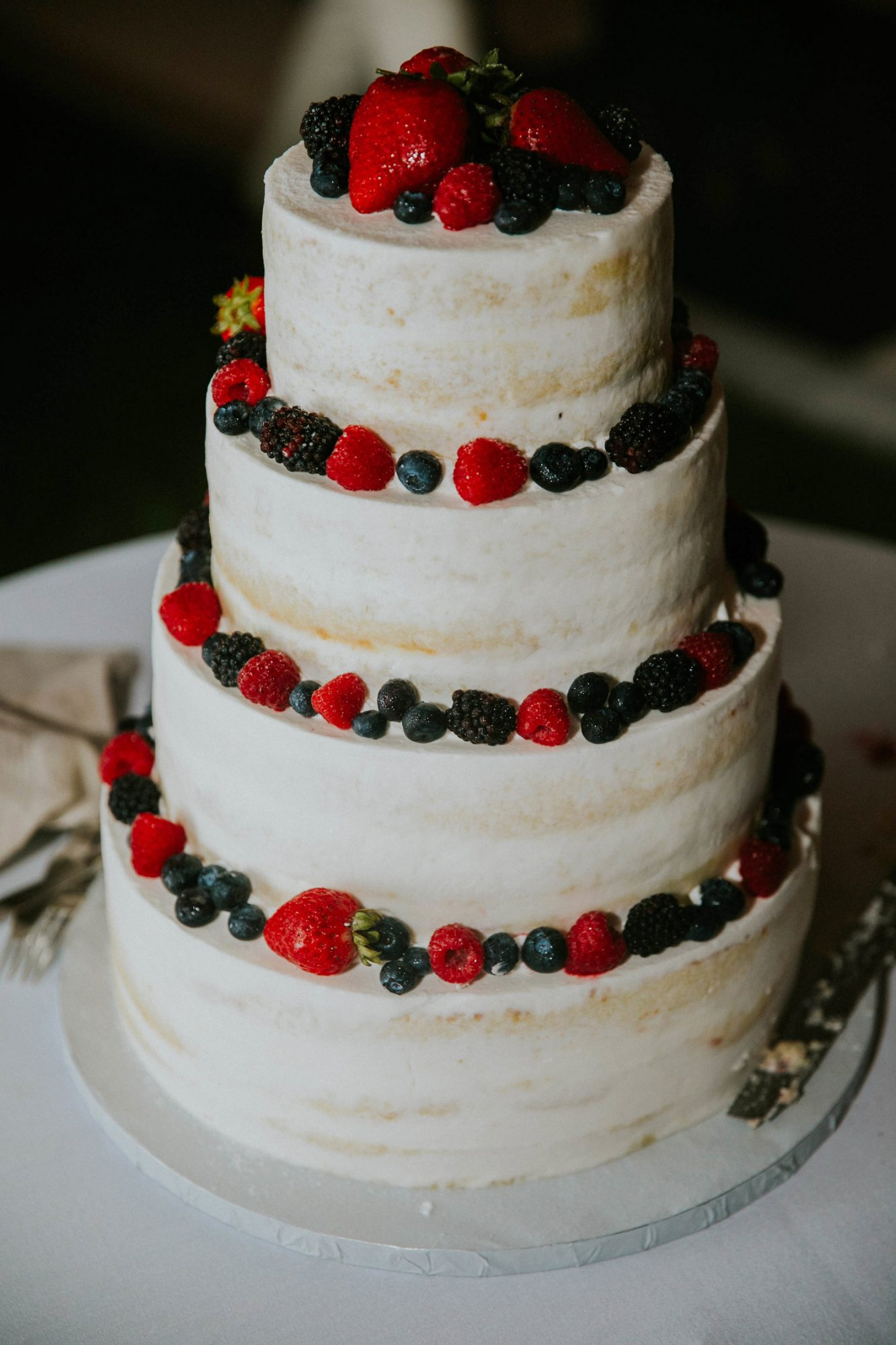white wedding cake with strawberries and blueberries