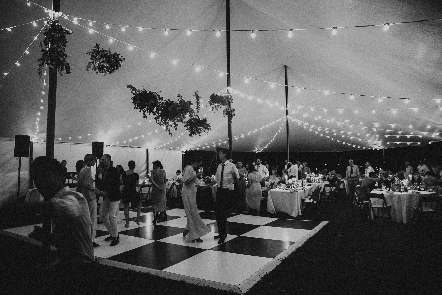 wedding dance floor with string lights and plants hanging above
