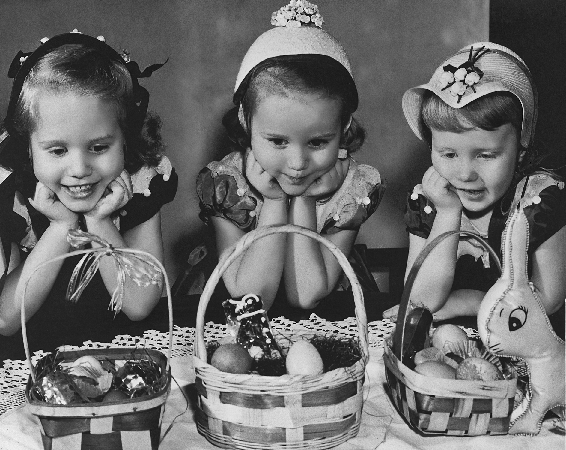 three girls in easter bonnets looking at baskets of candy