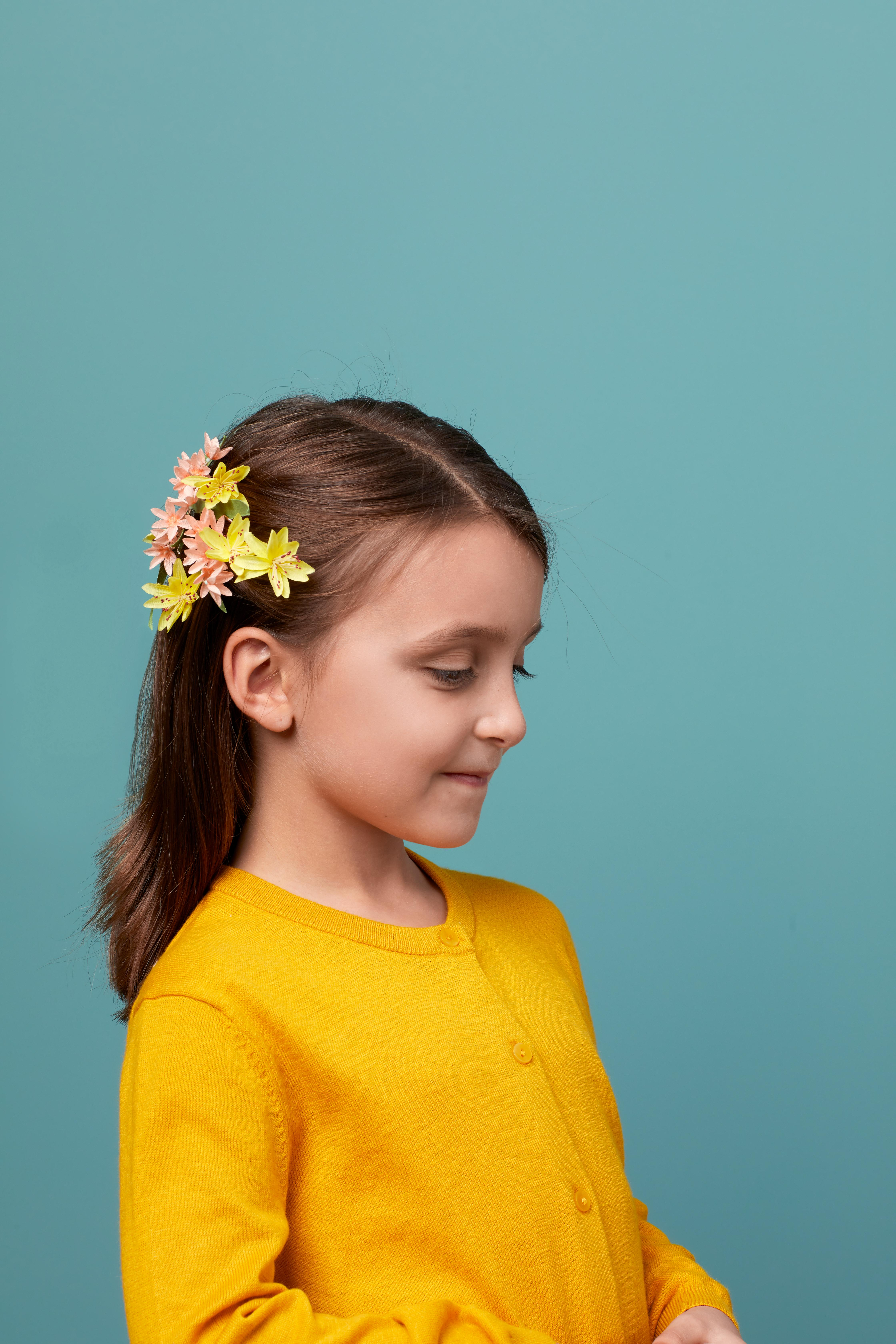 girl with yellow shirt wearing flower pin in hair