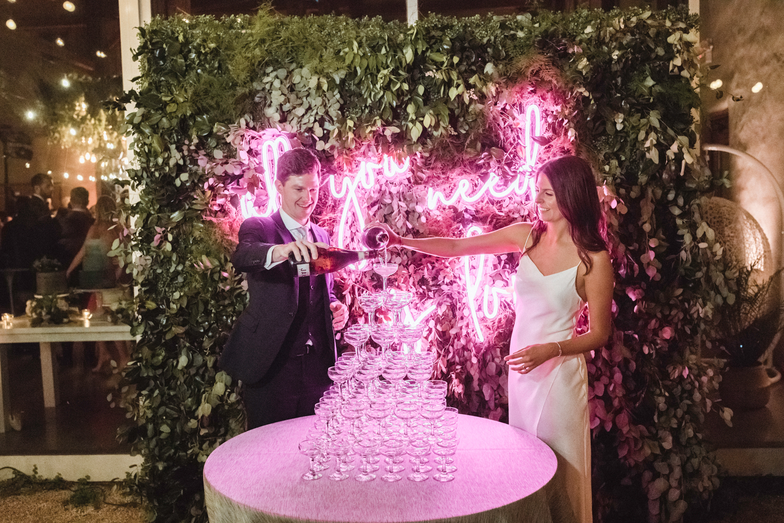 """""""All You Need Is Love"""" neon sign behind bride and groom"""