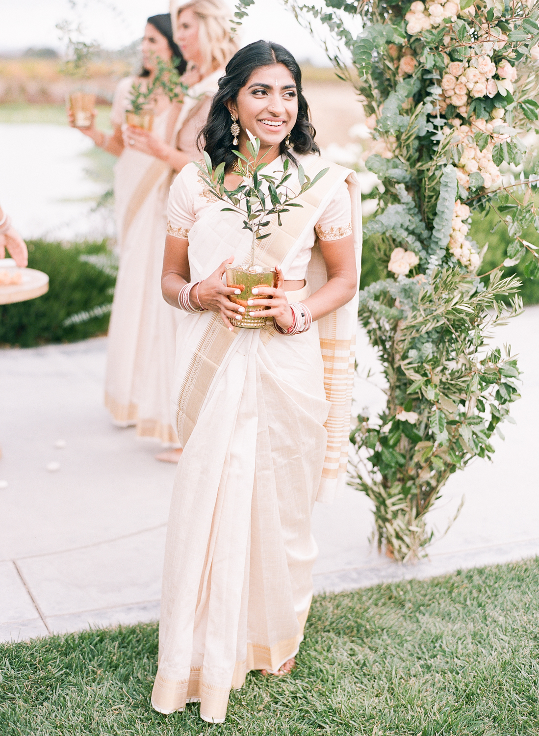 bridesmaids carrying gold votive jar holding olive tree