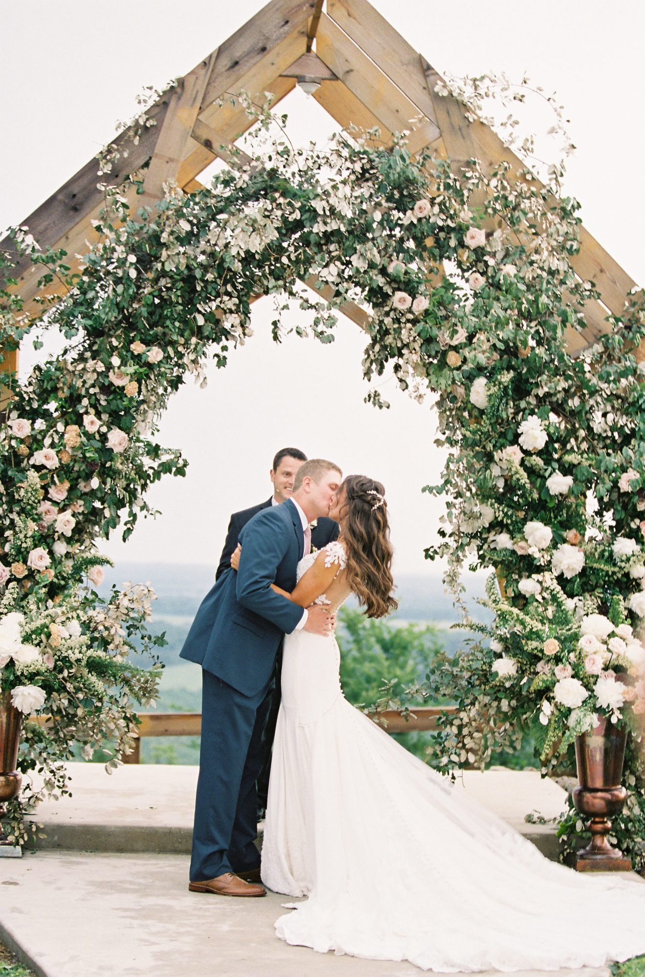 wedding couple kiss under floral archway