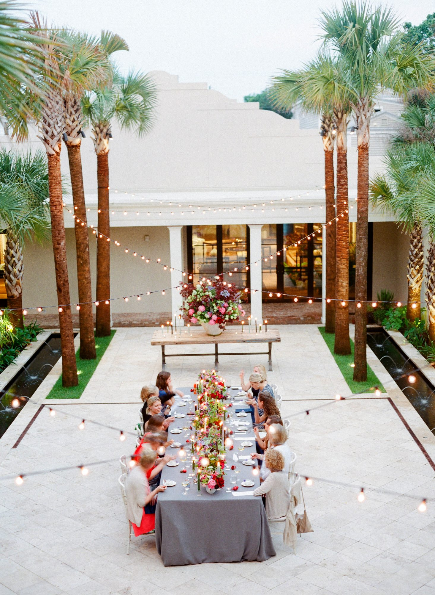 guests enjoying outdoor dinner with floral and candle centerpieces