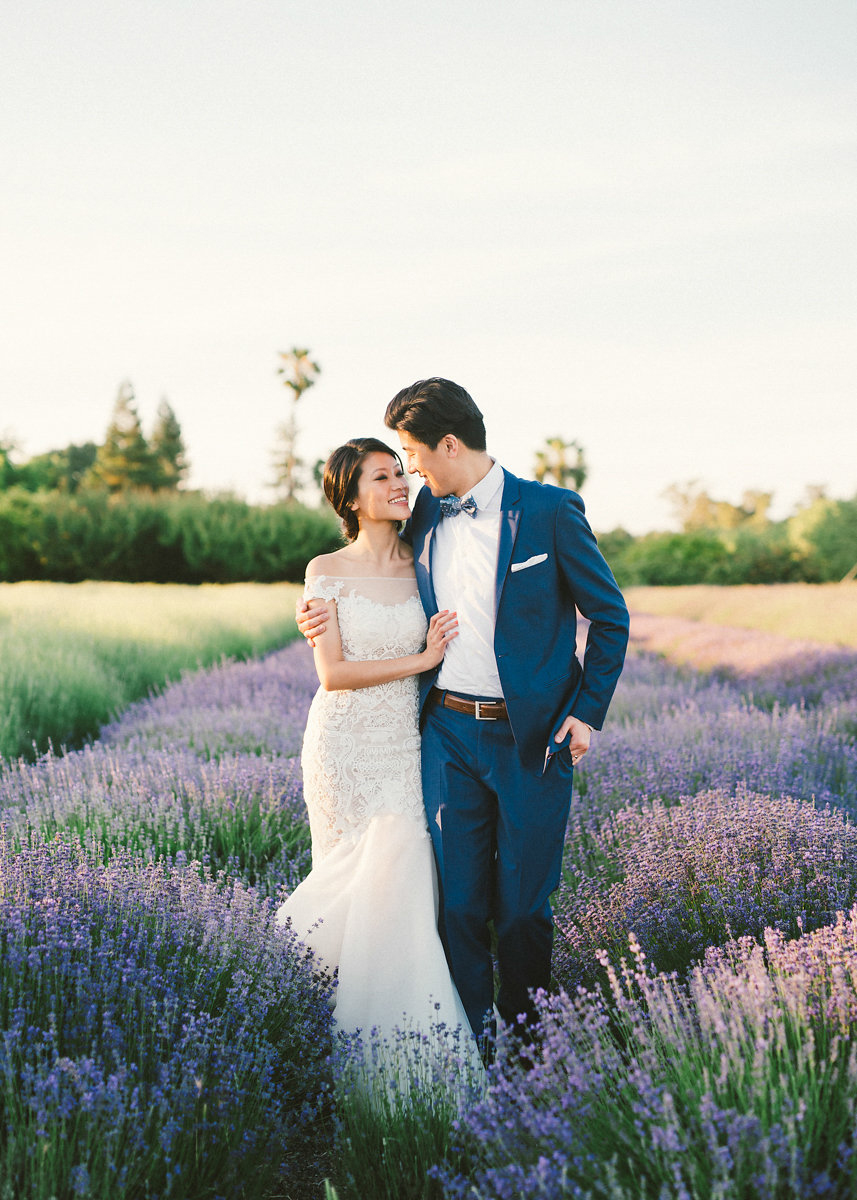 bride and groom pose in wedding attire within a lavender field