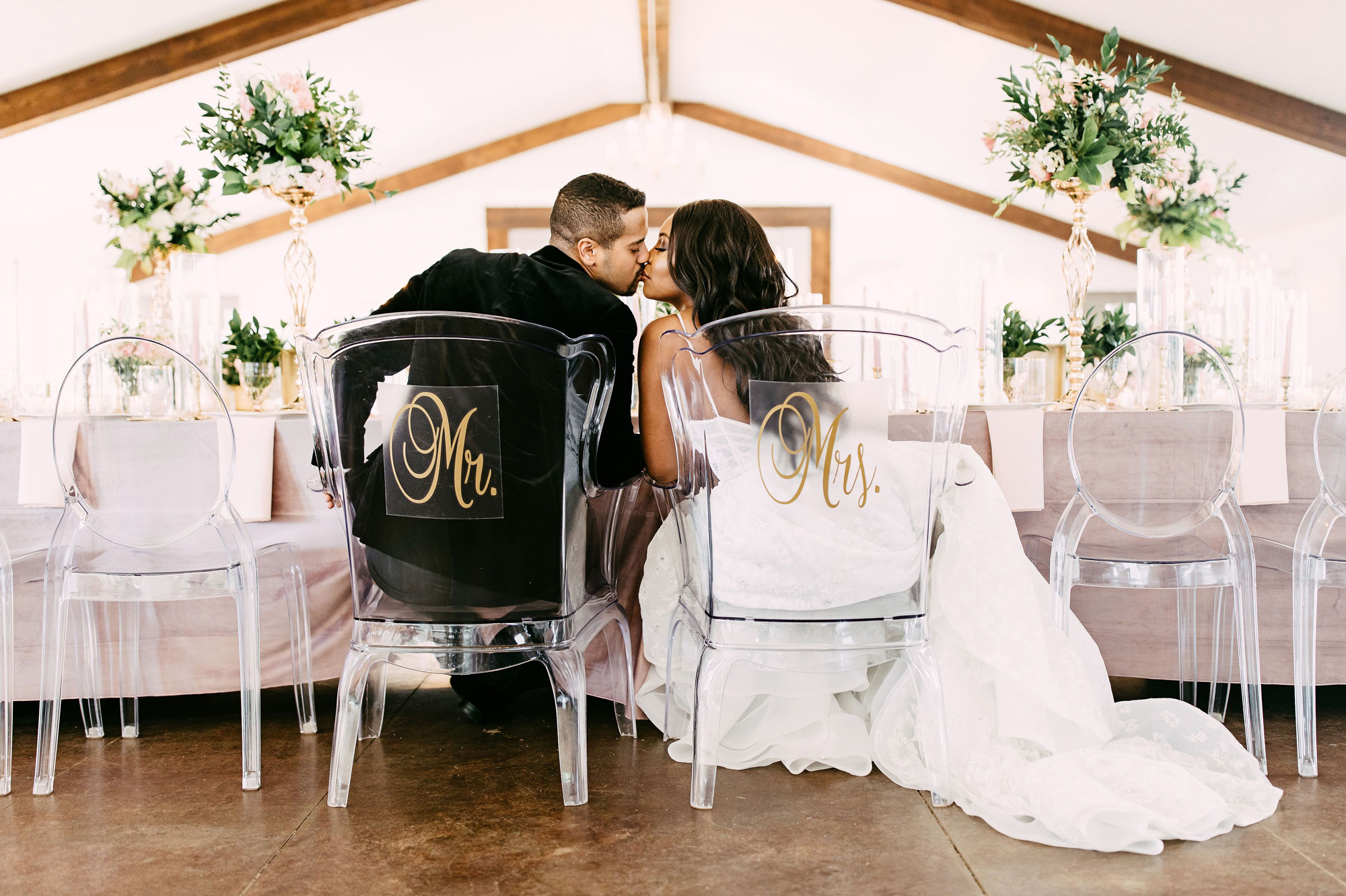 bride and groom kissing while sitting in mr and mrs chairs