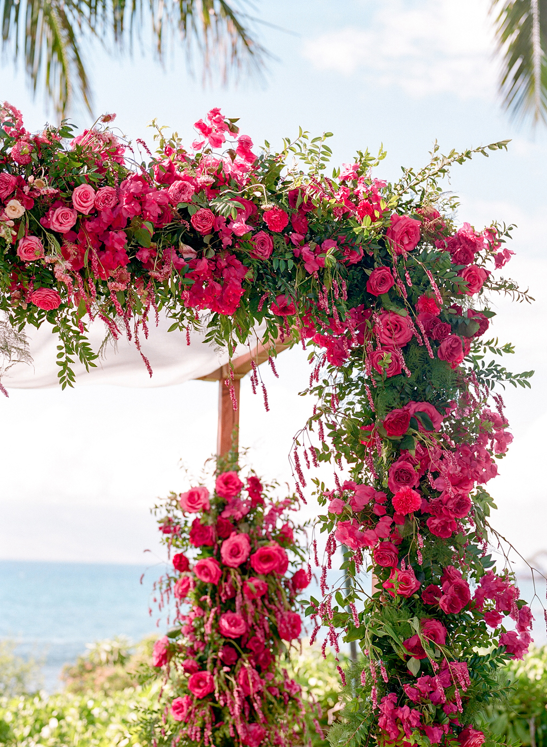 fuchsia-colored flowers and greenery covered chuppah