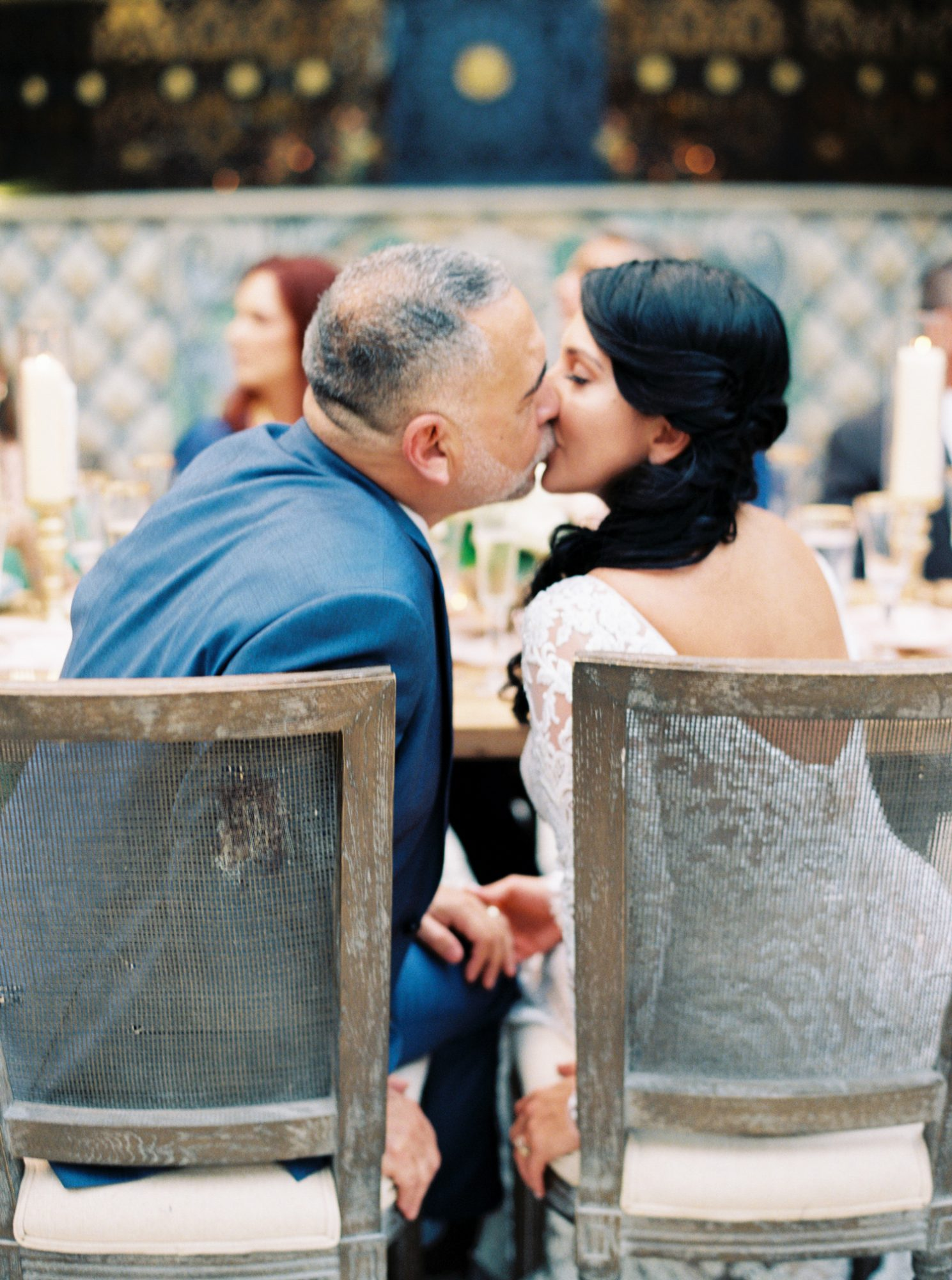 bride and groom kiss at wedding reception table after the wedding