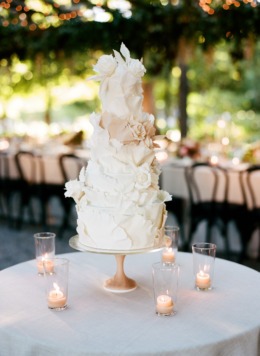 four laired wedding cake with petal frosted texture design in white and beige