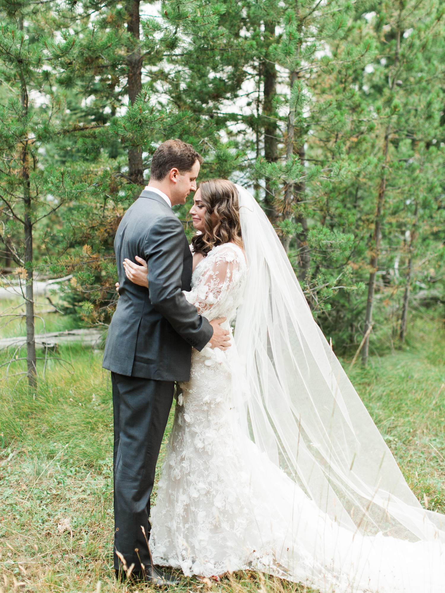 bride and groom hold each other on mountain hillside for portrait photo