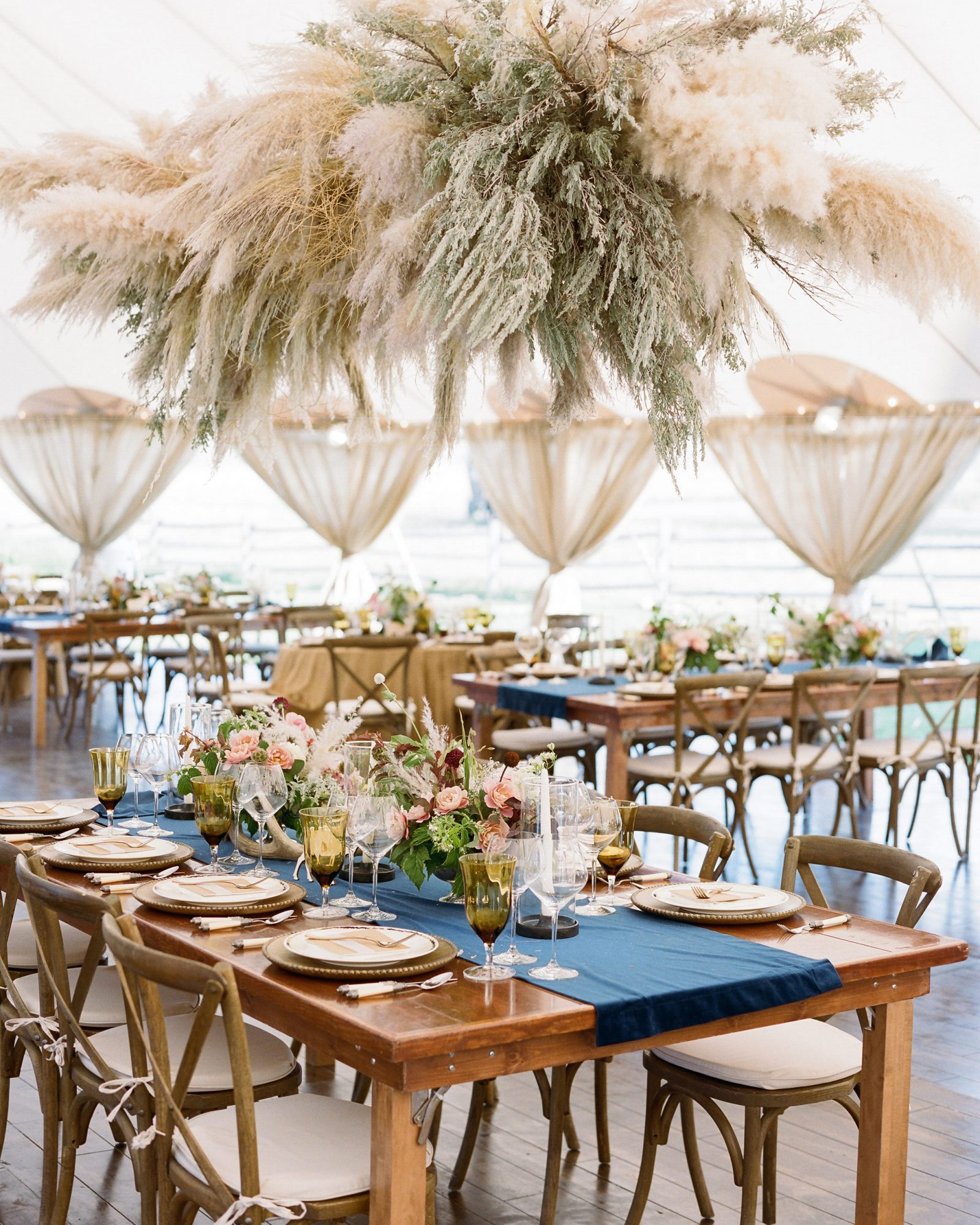 rehearsal dinner tables overhead pampas grass installation