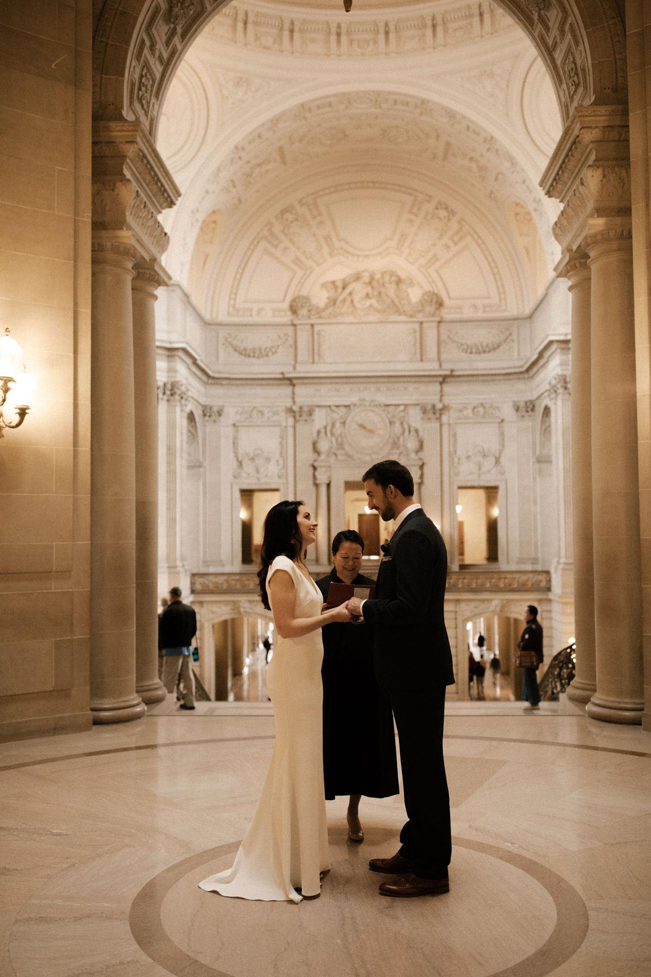 bride and groom standing in marble entryway at city hall
