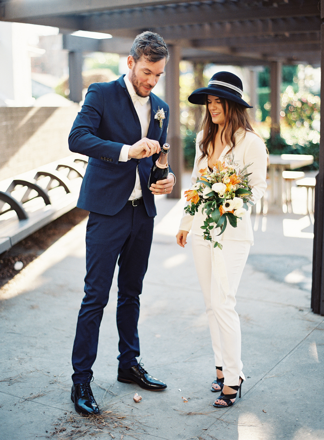 bride wearing white wedding suit standing with groom wearing navy suit