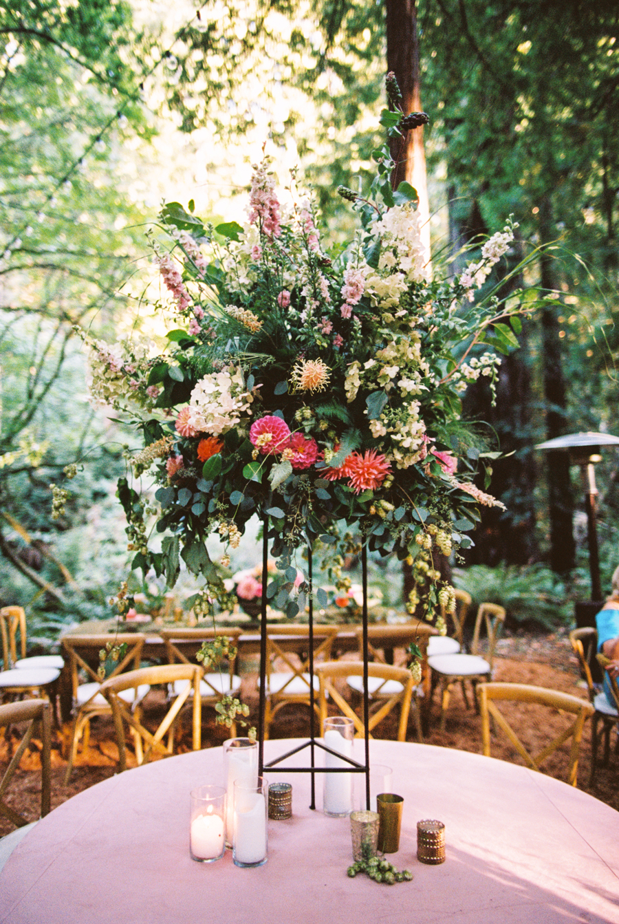 tall pink and green floral centerpiece in stand