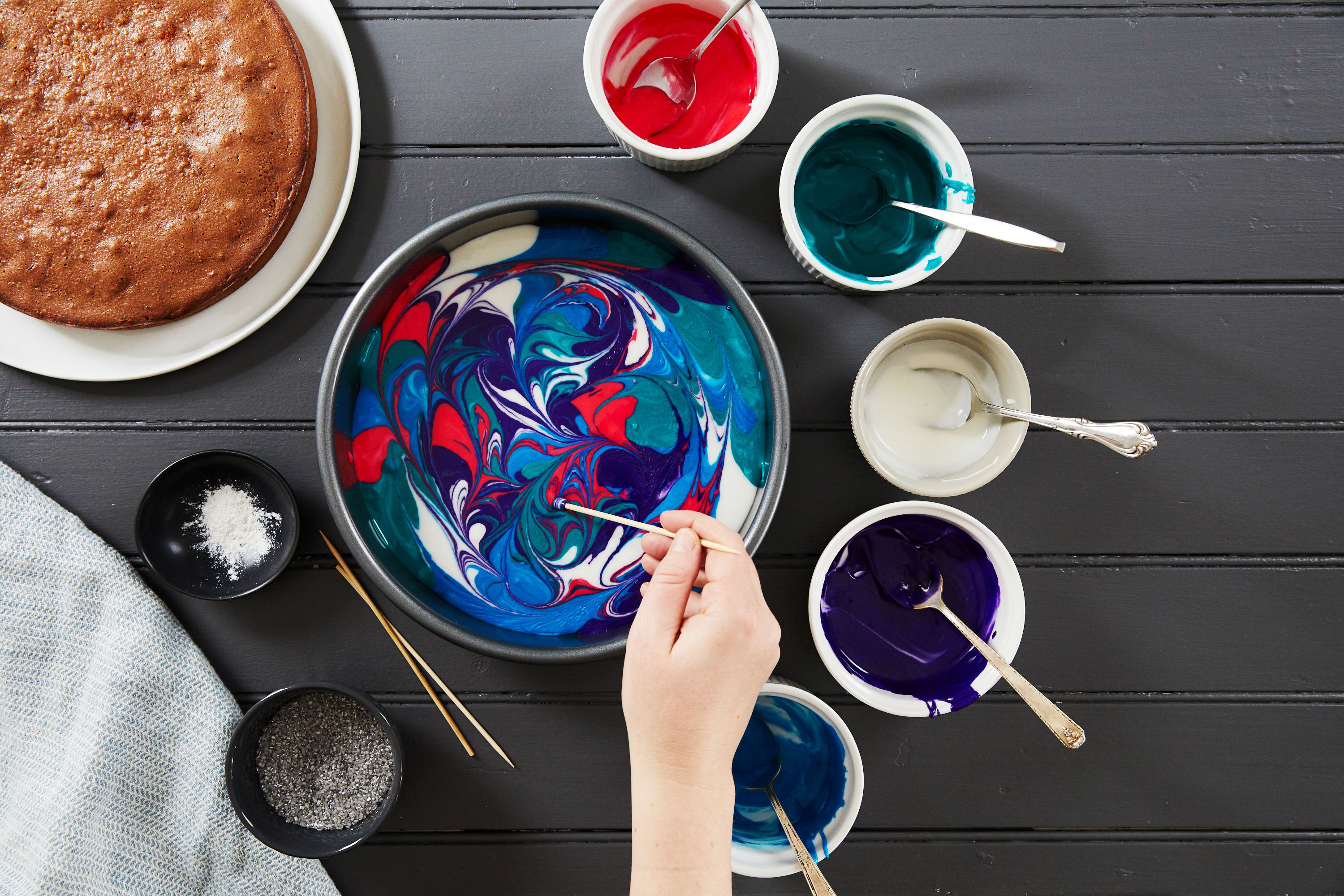 galaxy cake swirling frosting with toothpick