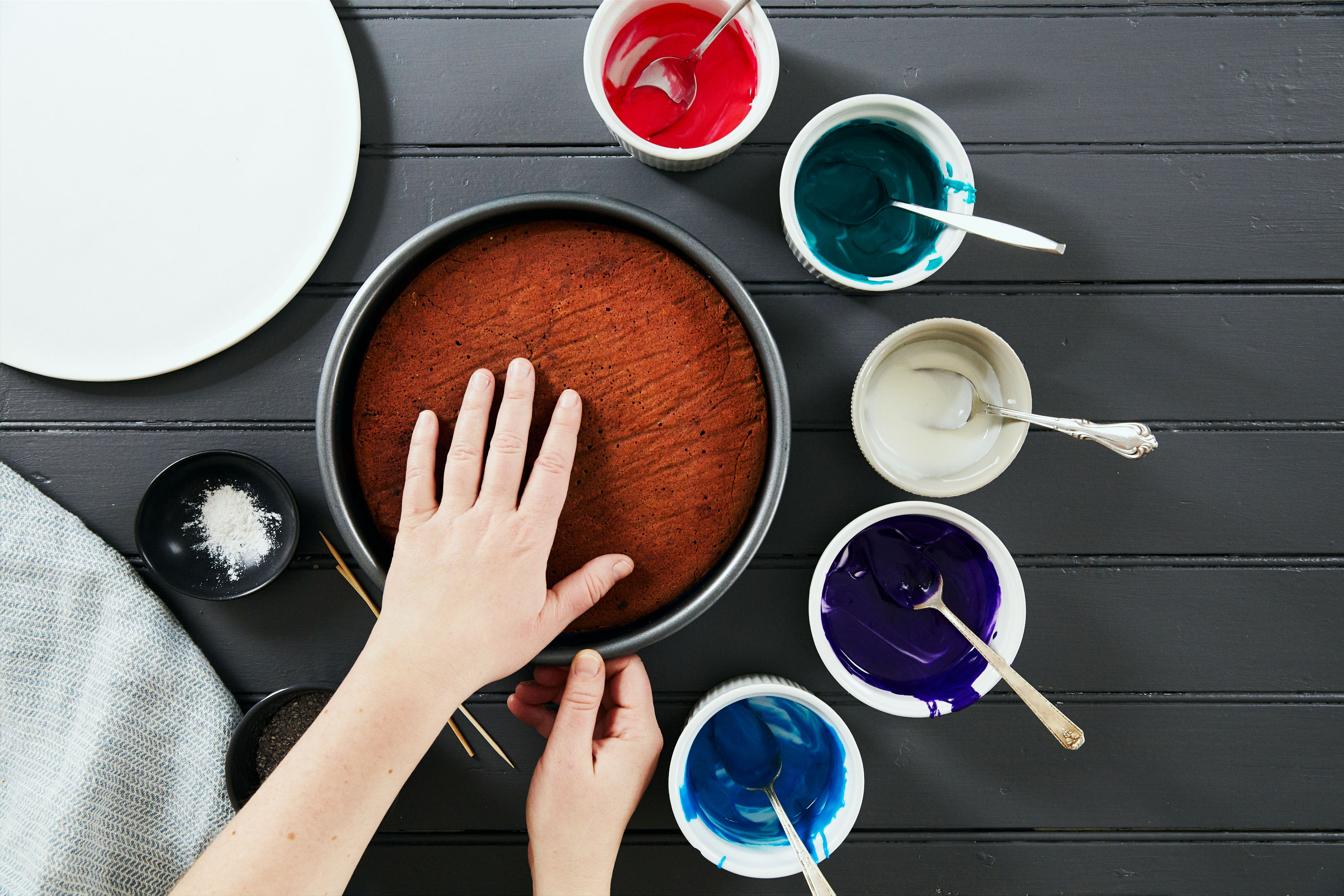 galaxy cake how-to with colored icing bowls hand on cake pan