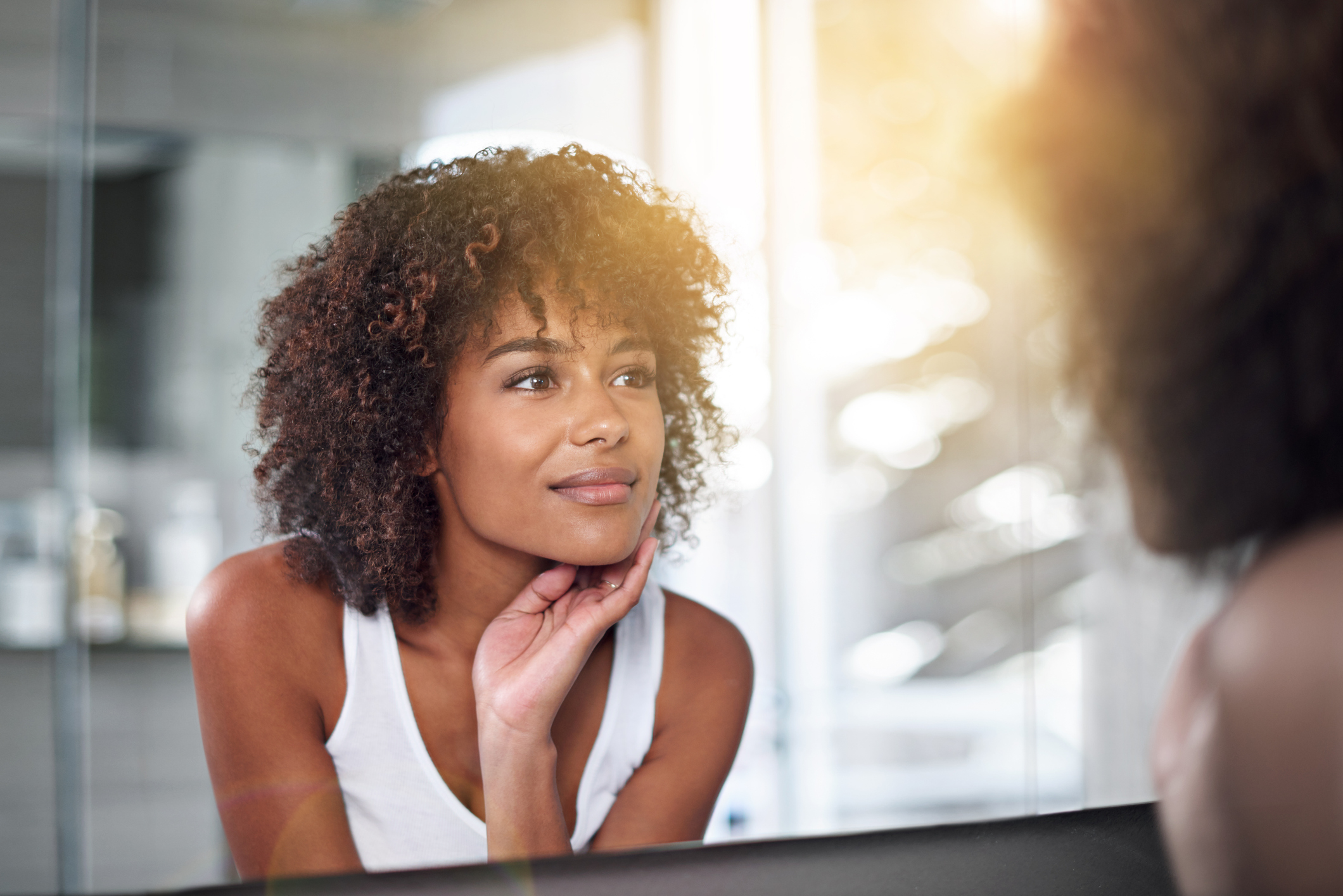 woman in mirror with glowing skin
