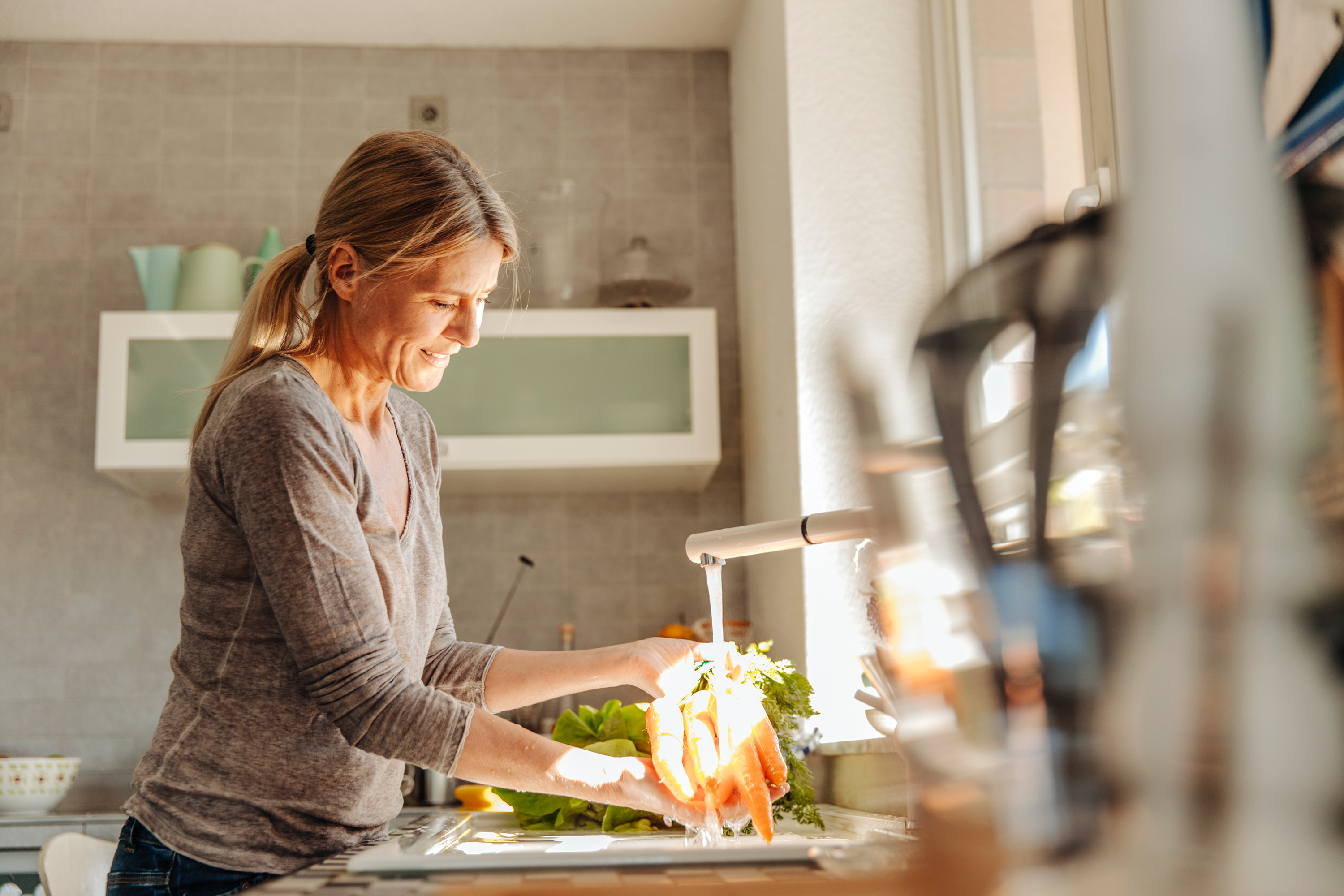 woman washing vegetables in her kitchen