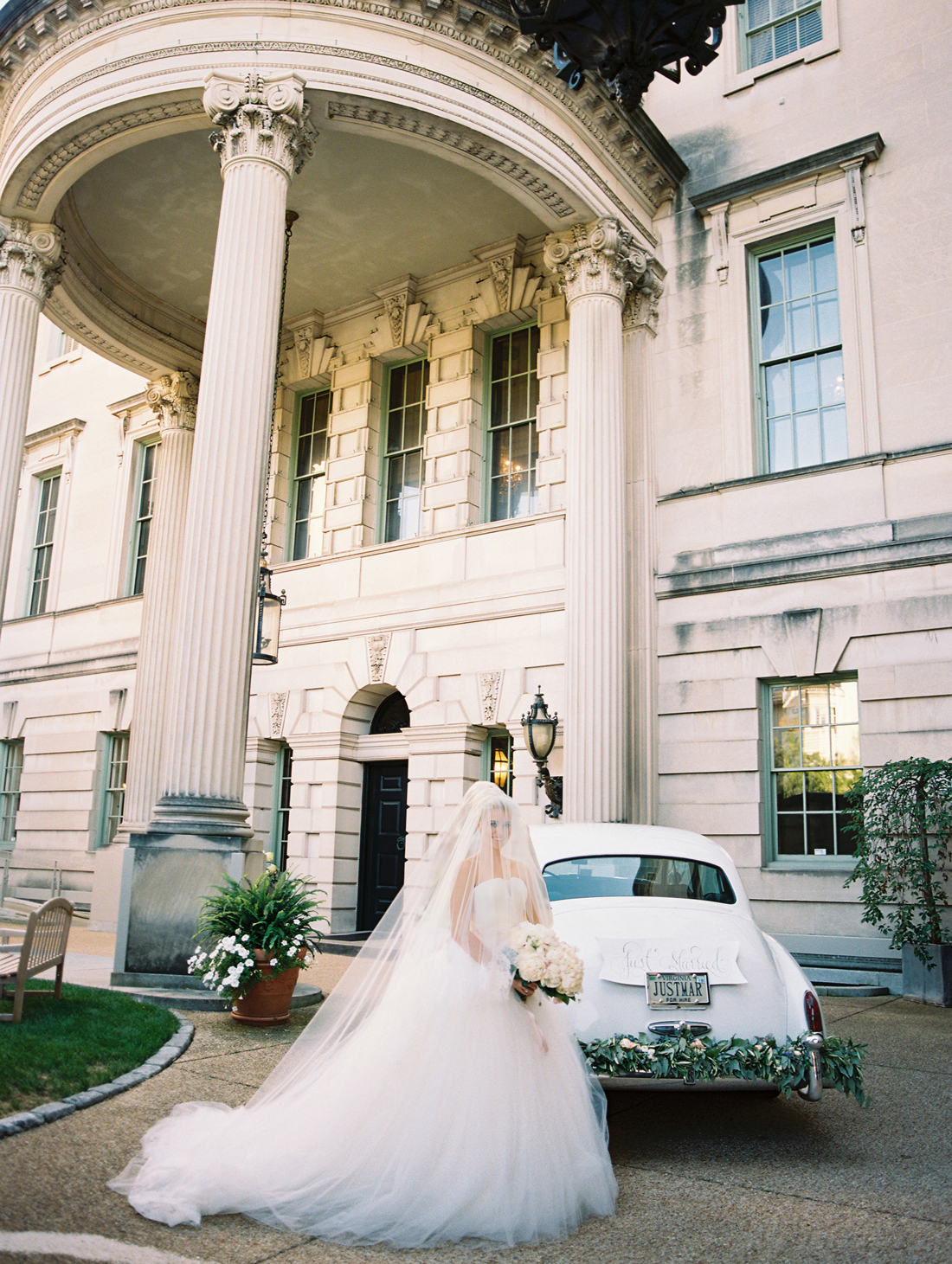 bride in wedding dress outside venue next to vintage white car