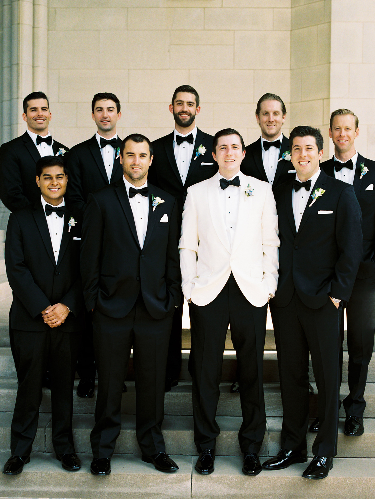 groomsmen wearing matching classic tuxedos standing with groom