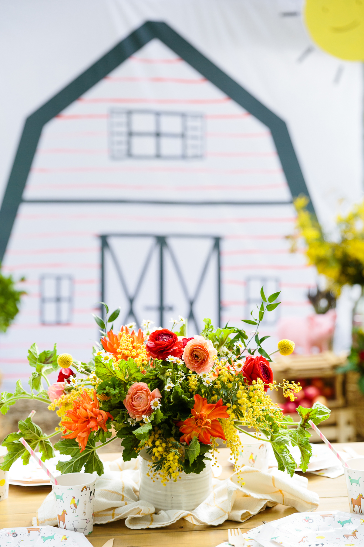 charlottes web childrens party flowers on table with barn backdrop in background