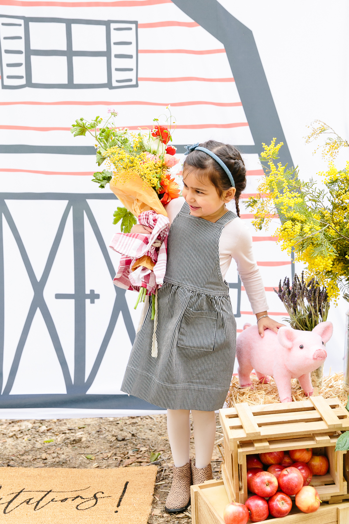 charlottes web childrens party girl holding flowers posing in front of barn backdrop with pig stuffed animal