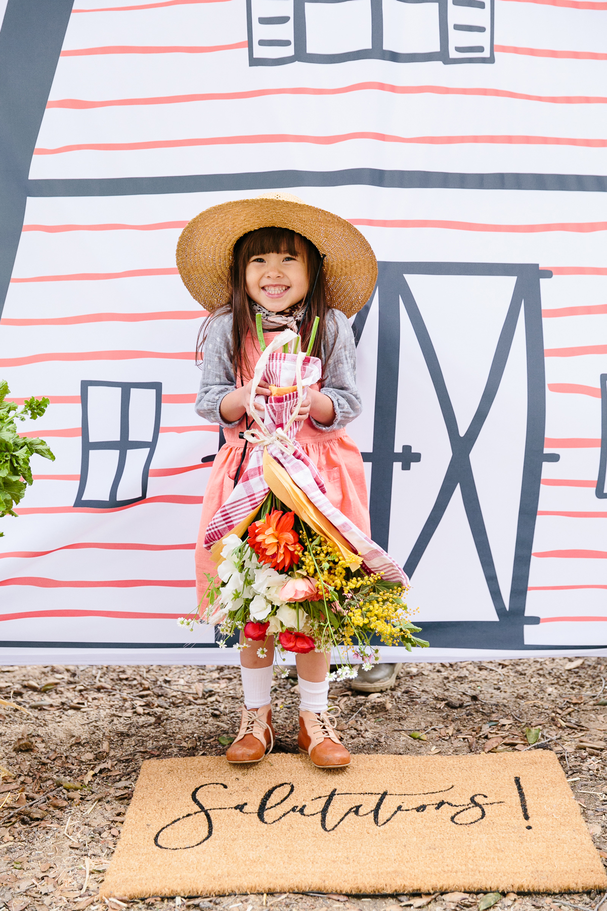 charlottes web childrens party girl holding flowers posing in front of barn backdrop