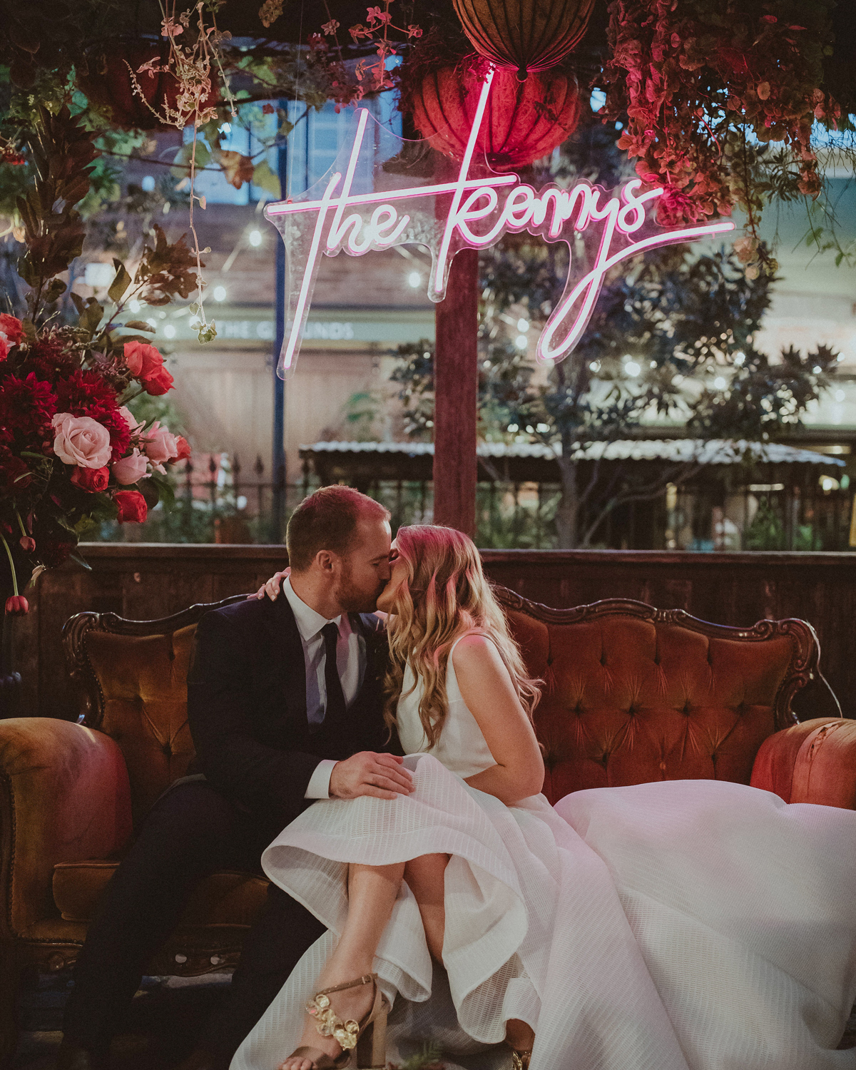 wedding after party bride and groom kissing on couch beneath neon sign