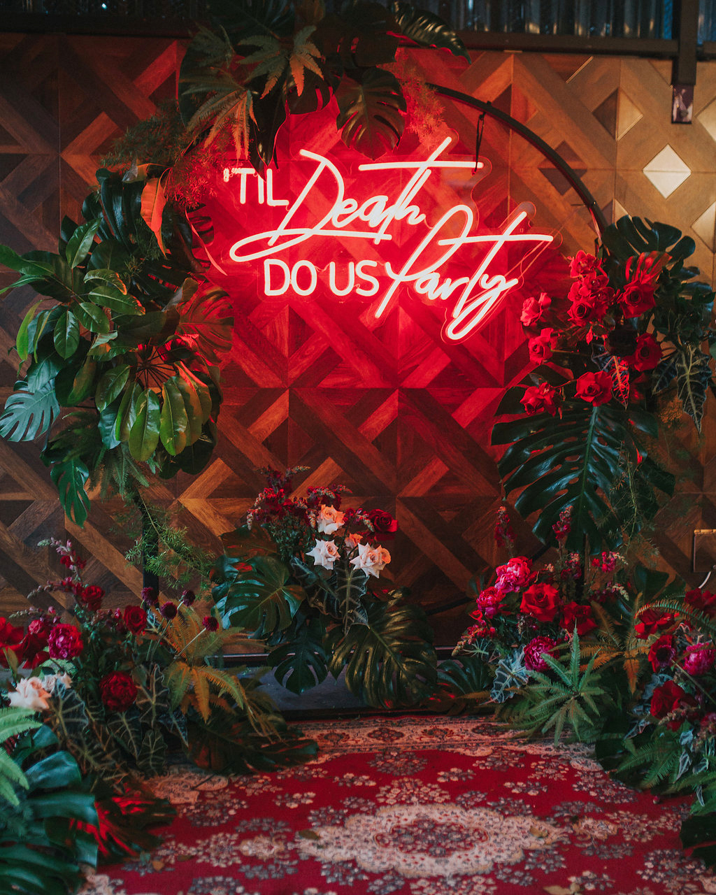 wedding after party plants surrounding neon sign