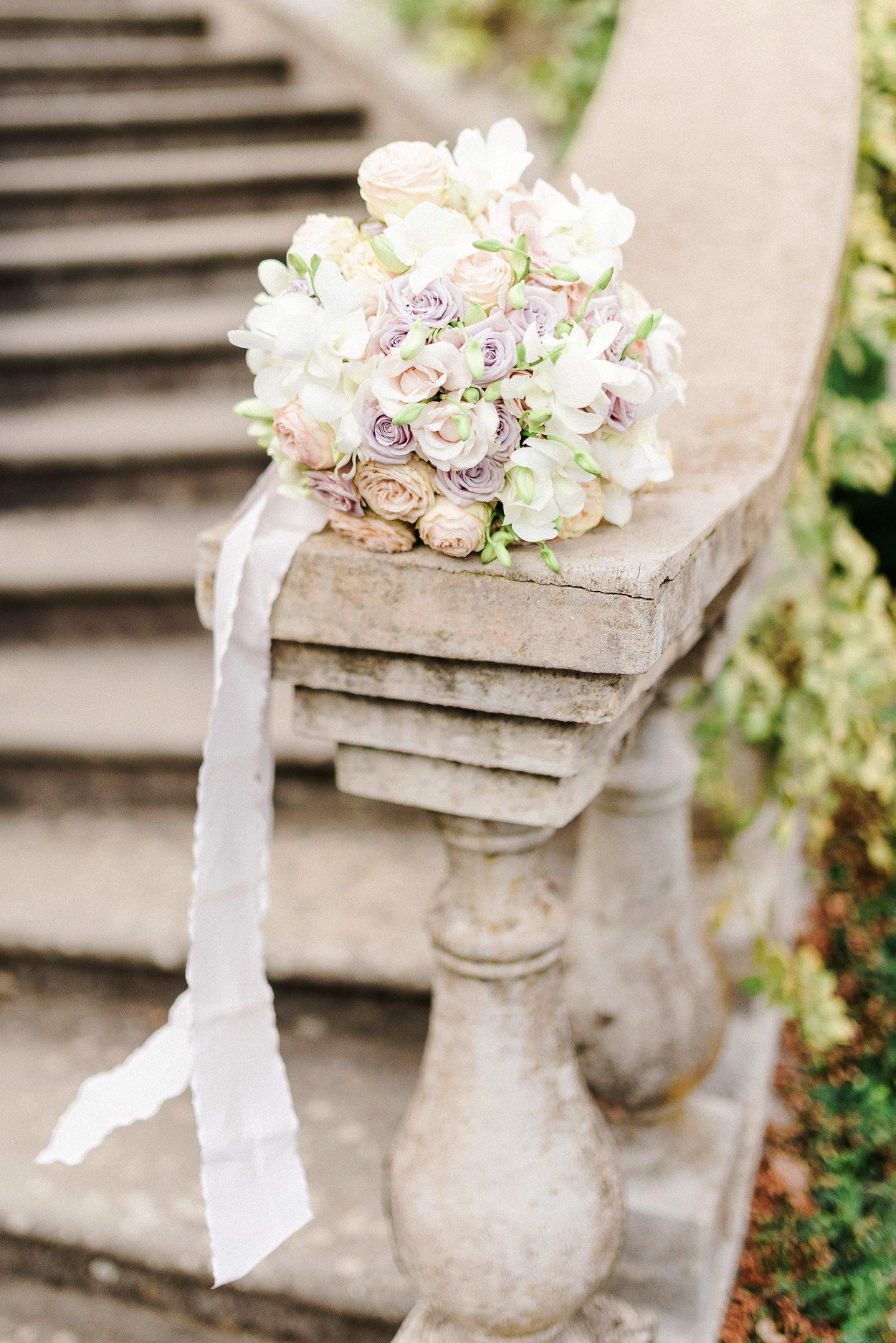 pastel colored floral wedding bouquet with white ribbon