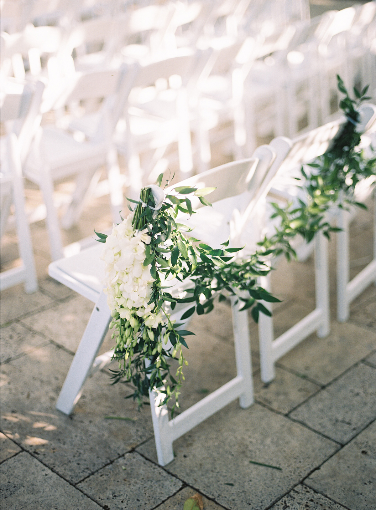 last row ceremony chair decorations white and green floral arrangement adorned to chairs