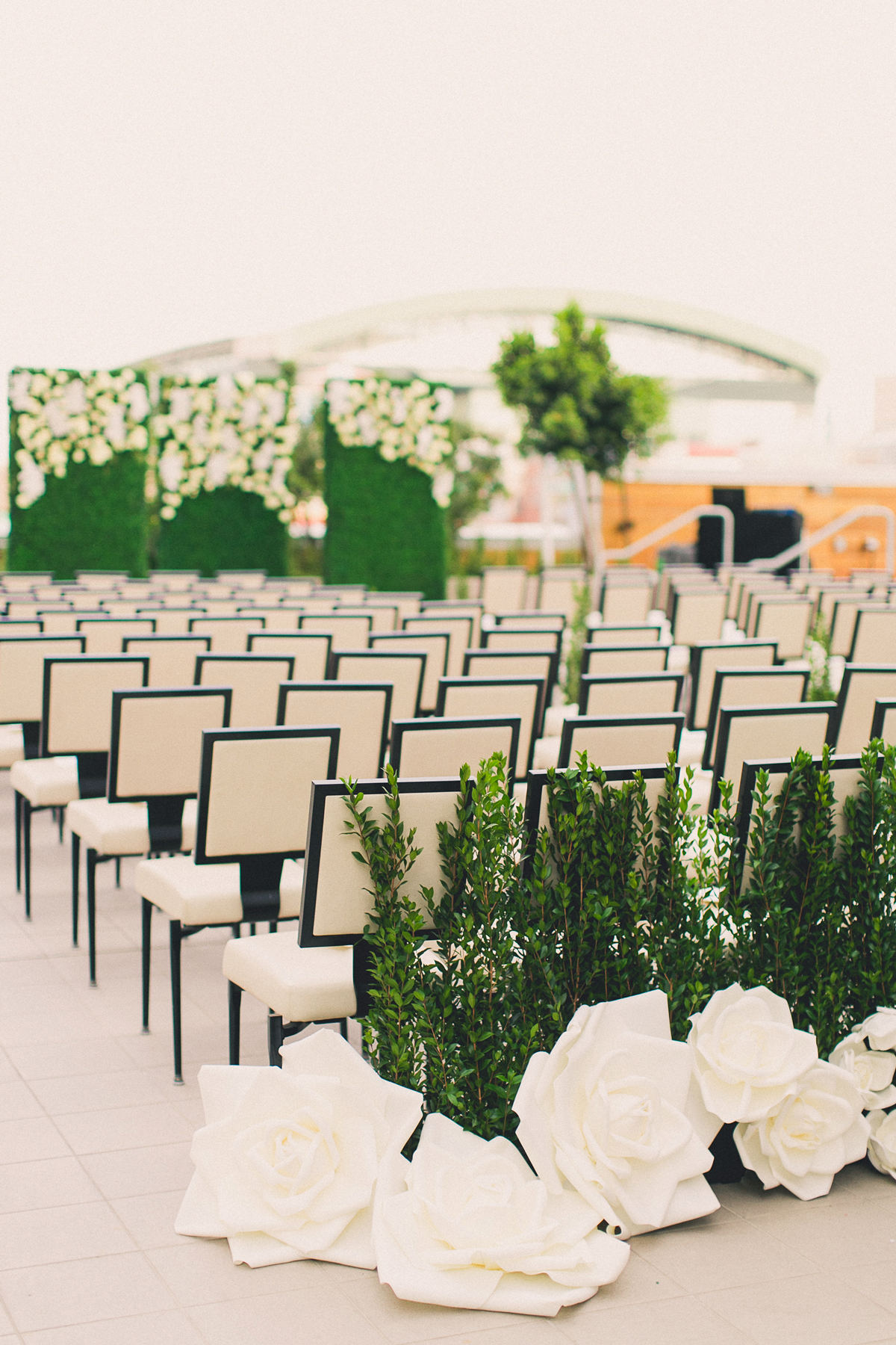 last row ceremony chair decorations oversized white roses and greenery