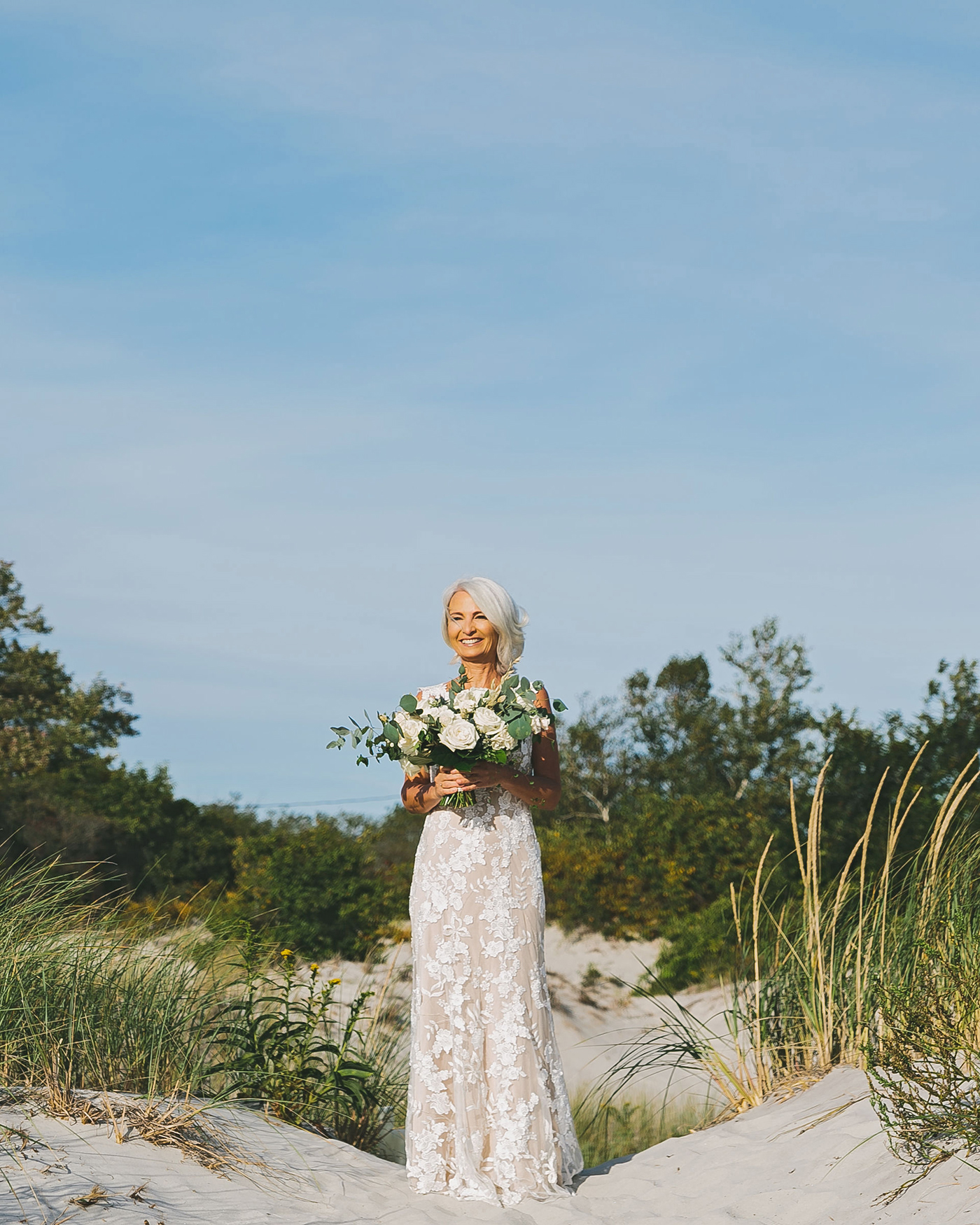 bride standing in sand and grass