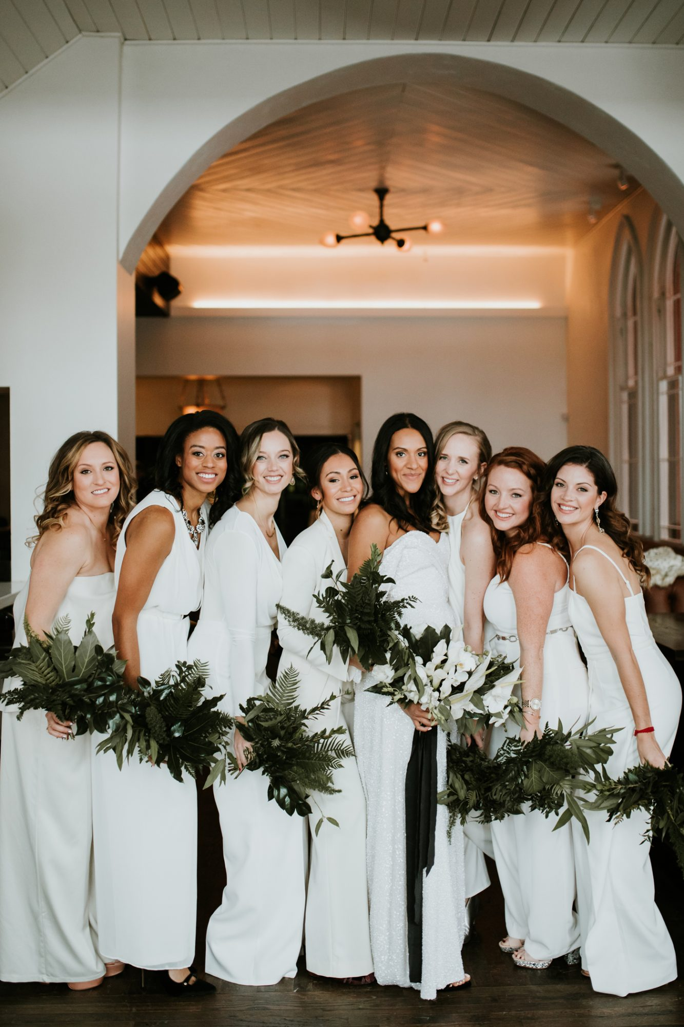 women wearing white bridesmaids jumpsuits holding greenery bouqets