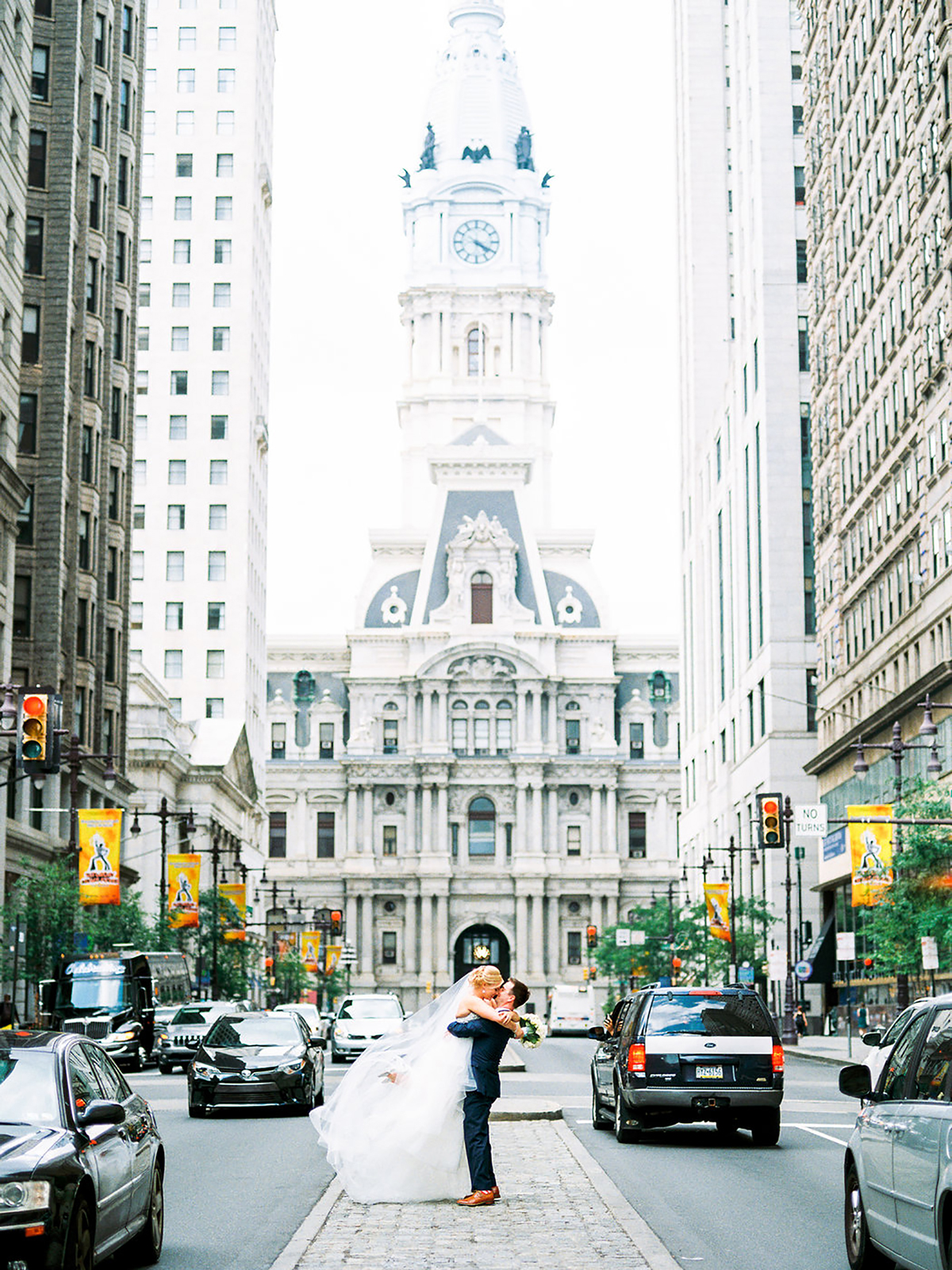 city hall wedding bride and groom kissing on median in front of philadelphia city hall