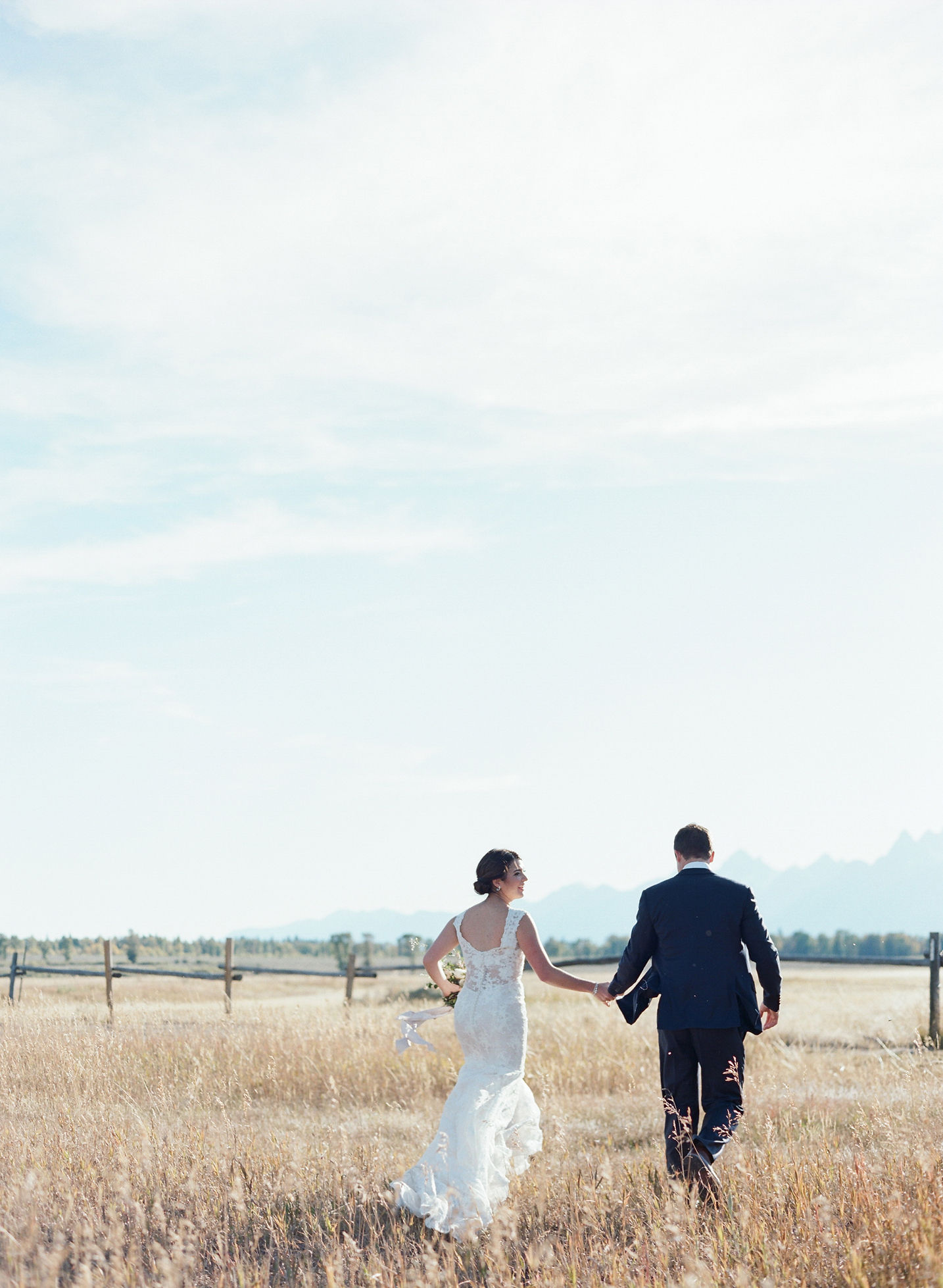 bride and groom running at jackson hole outside