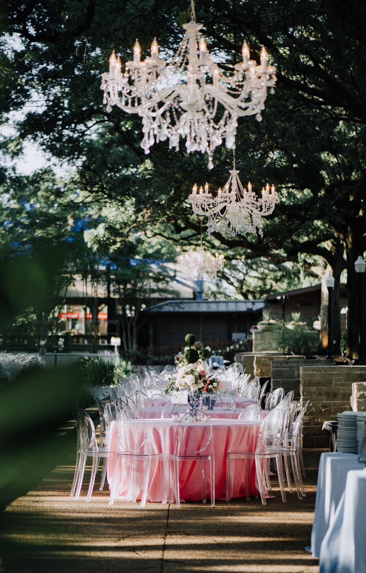 cathleen and winston wedding outdoor reception pink table settings beneath chandeliers