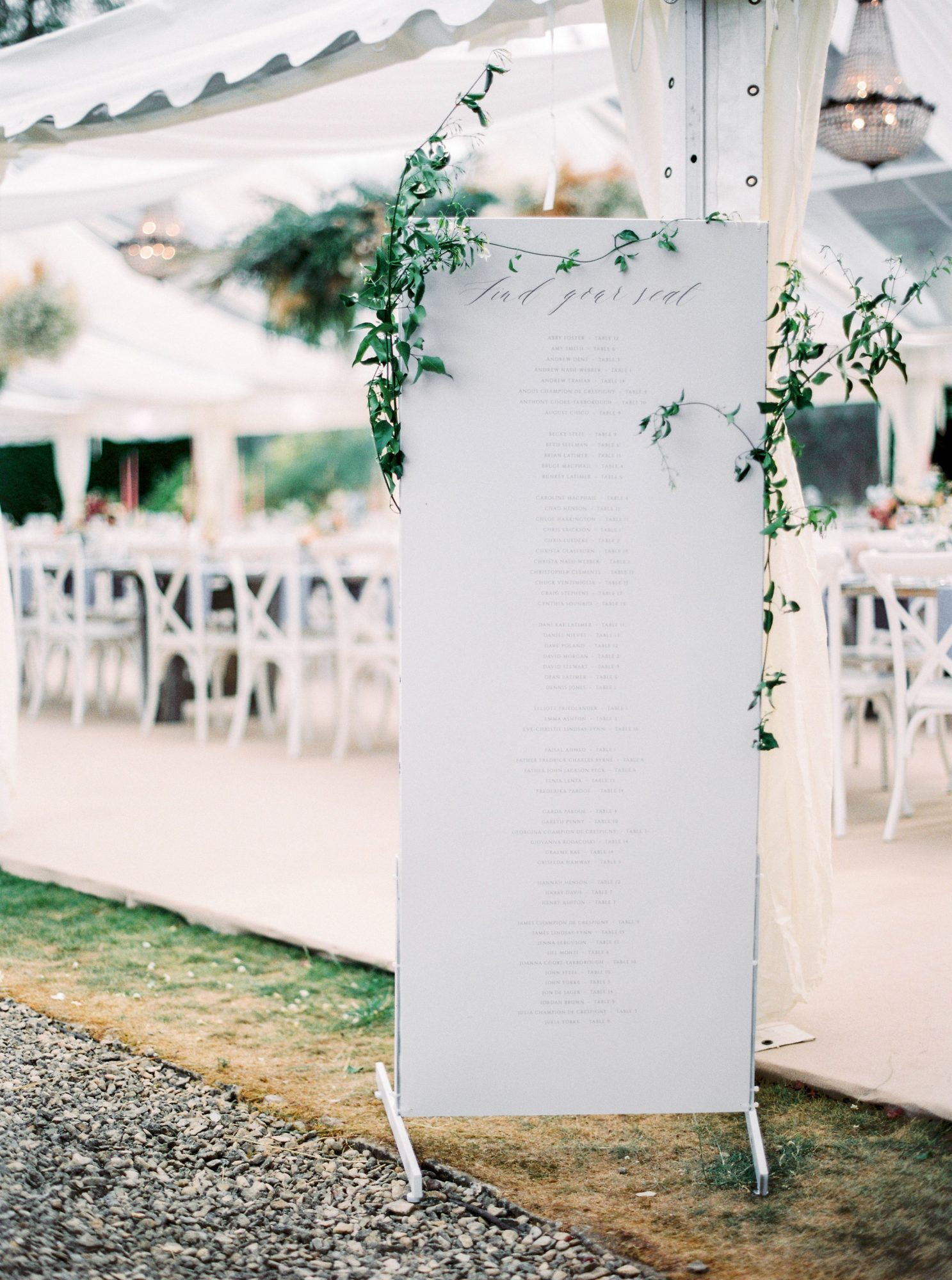 simple white seating chart with greenery decor