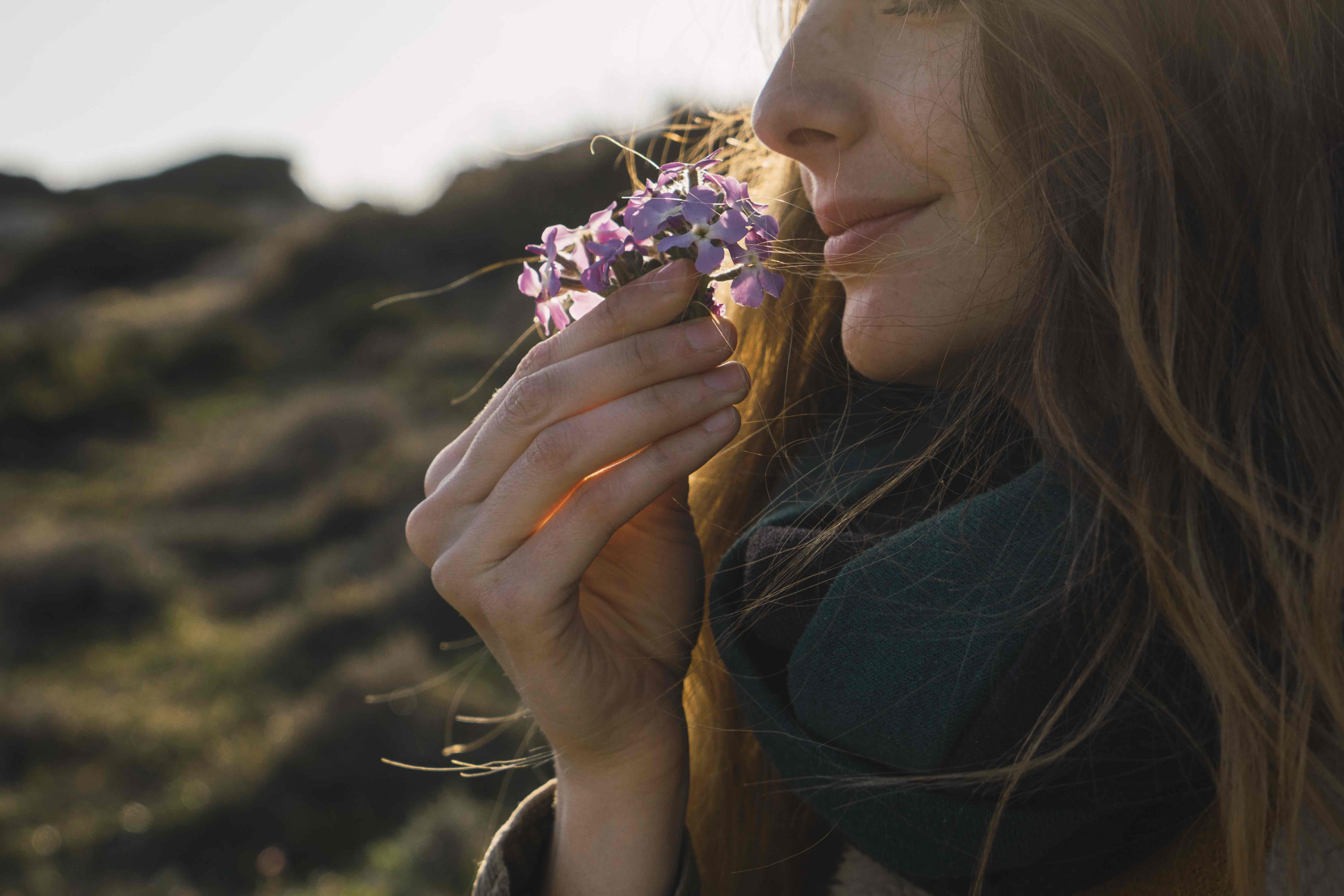 woman smelling flower outdoors