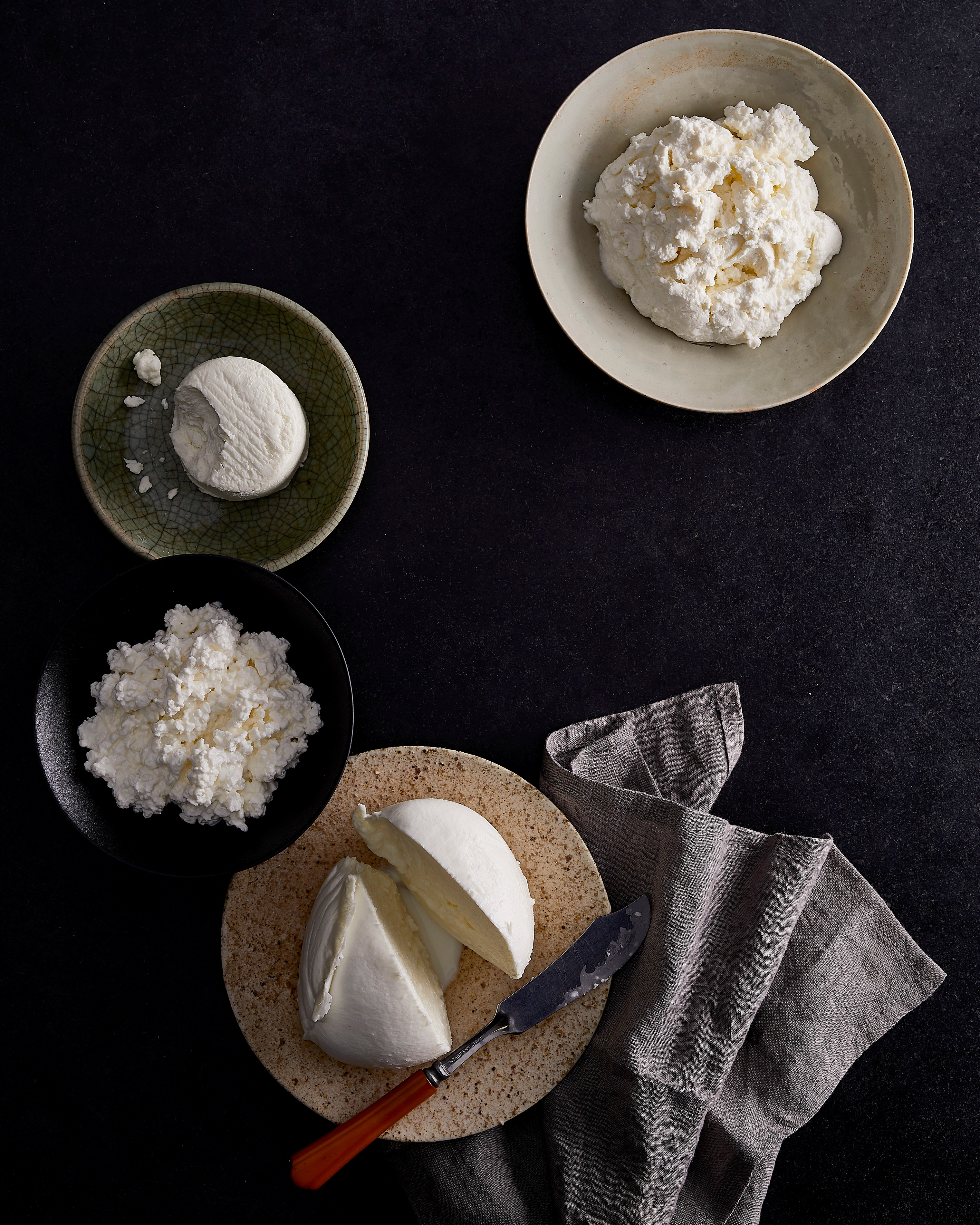 bowls and plate of assorted soft cheese