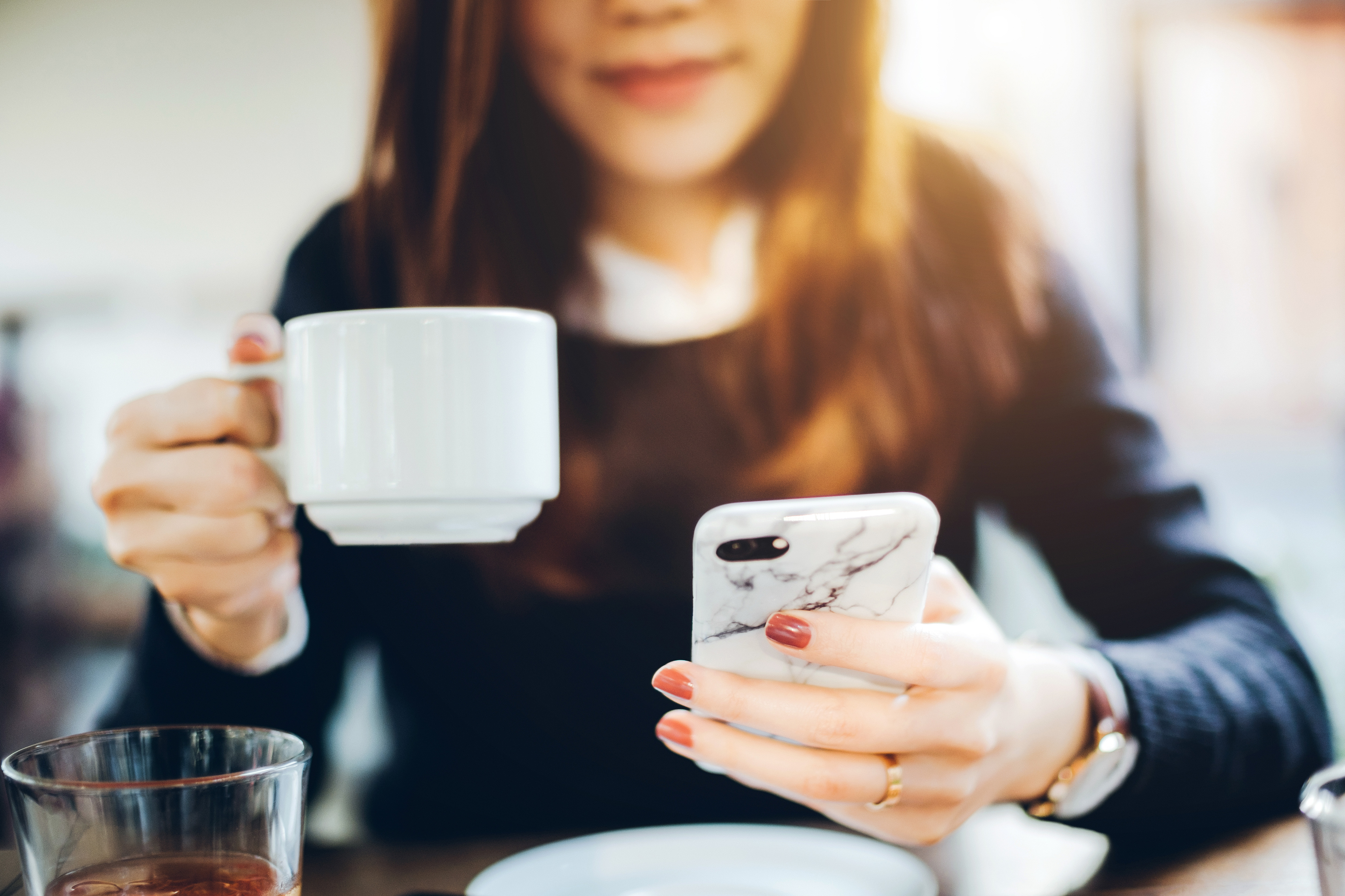 Woman Looking at Cell Phone Will Drinking Coffee