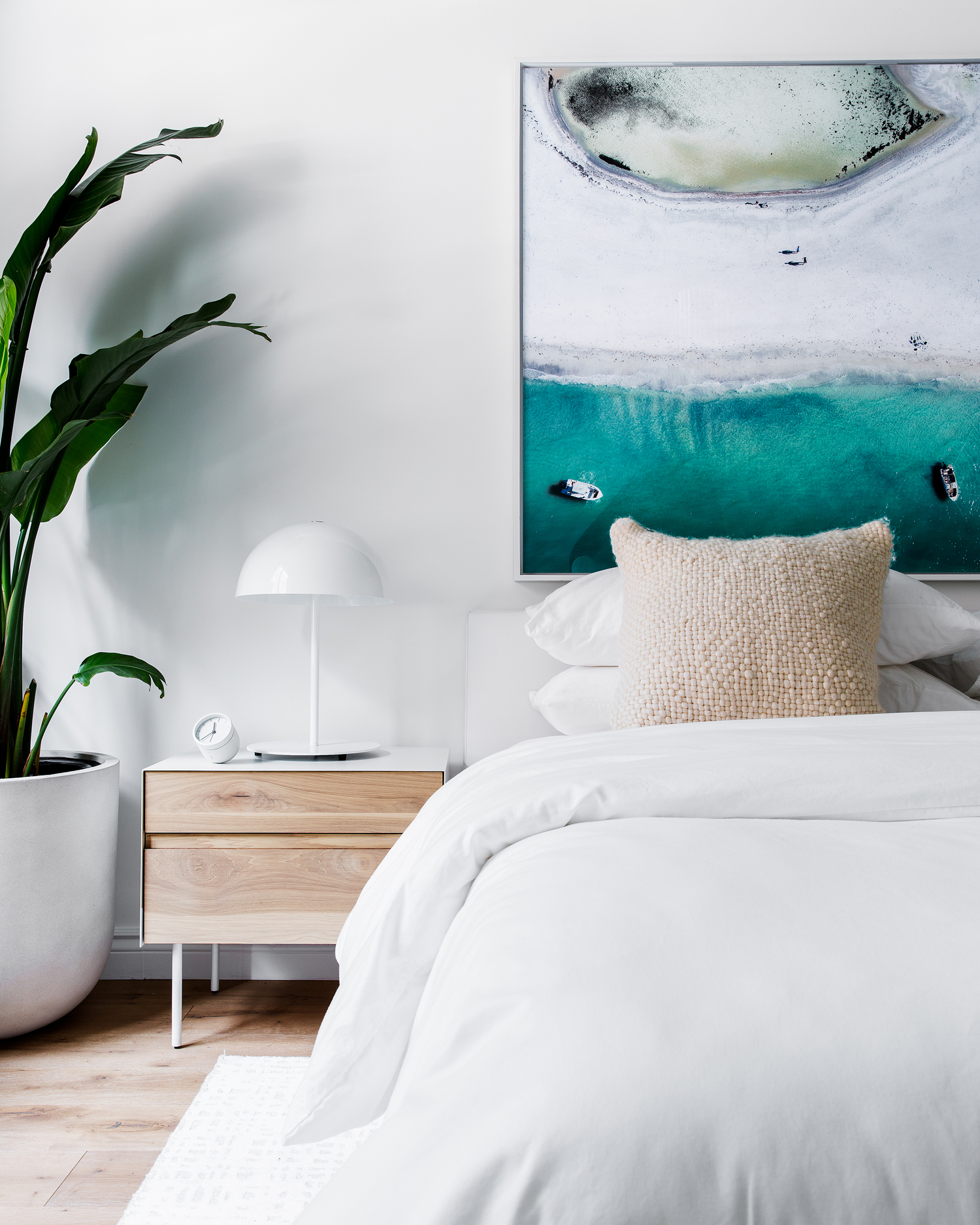 neutral bedroom with palm tree and abstract oceanic photograph above bed
