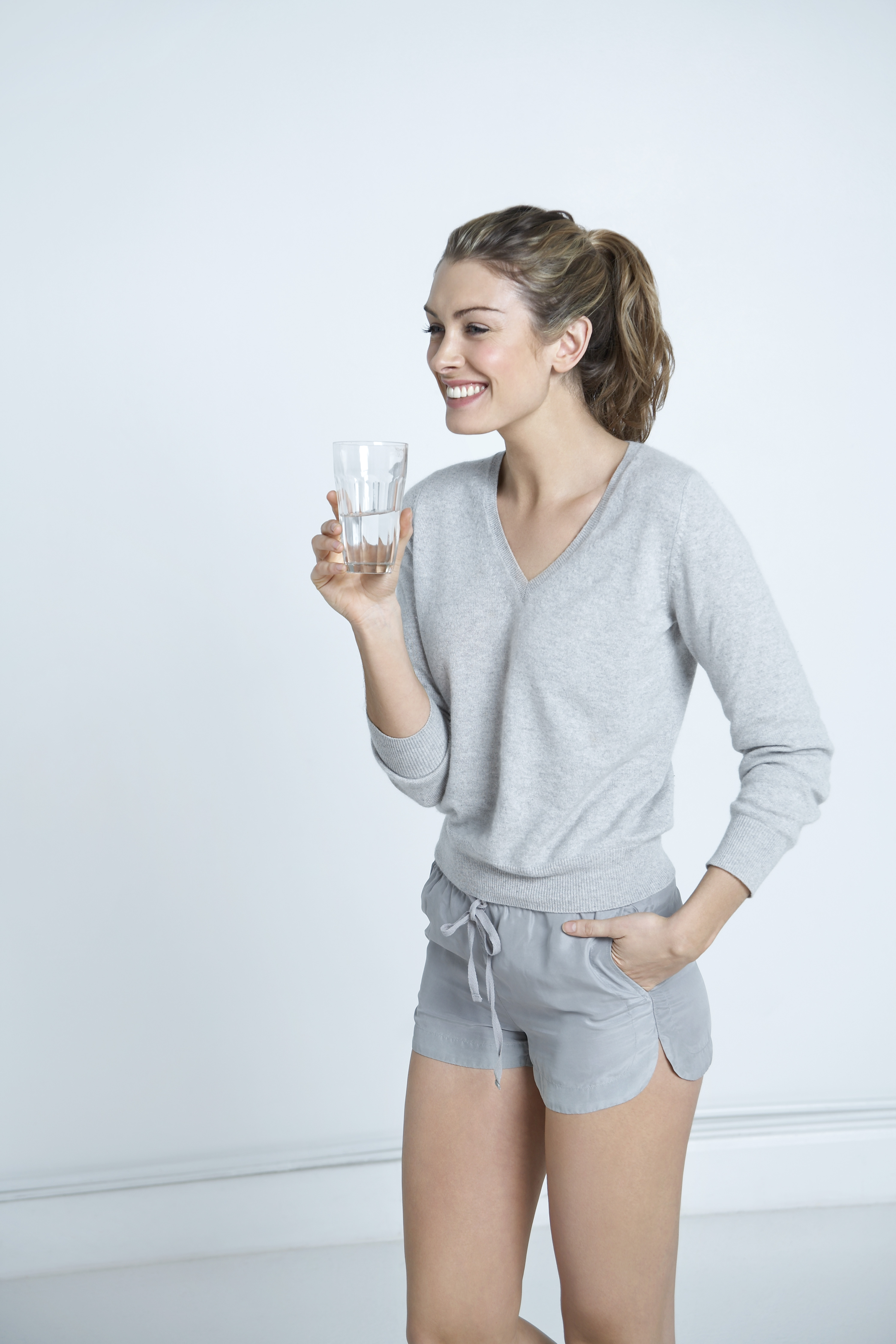 woman drinking water out of a glass